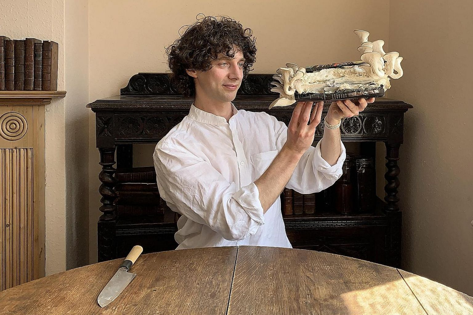 Close-up of a copy of Merlin Sheldrake's Entangled Life. He seeded the book with a variety of oyster mushroom that ate its way through the book. British biologist Merlin Sheldrake holding a copy of his debut book, Entangled Life.