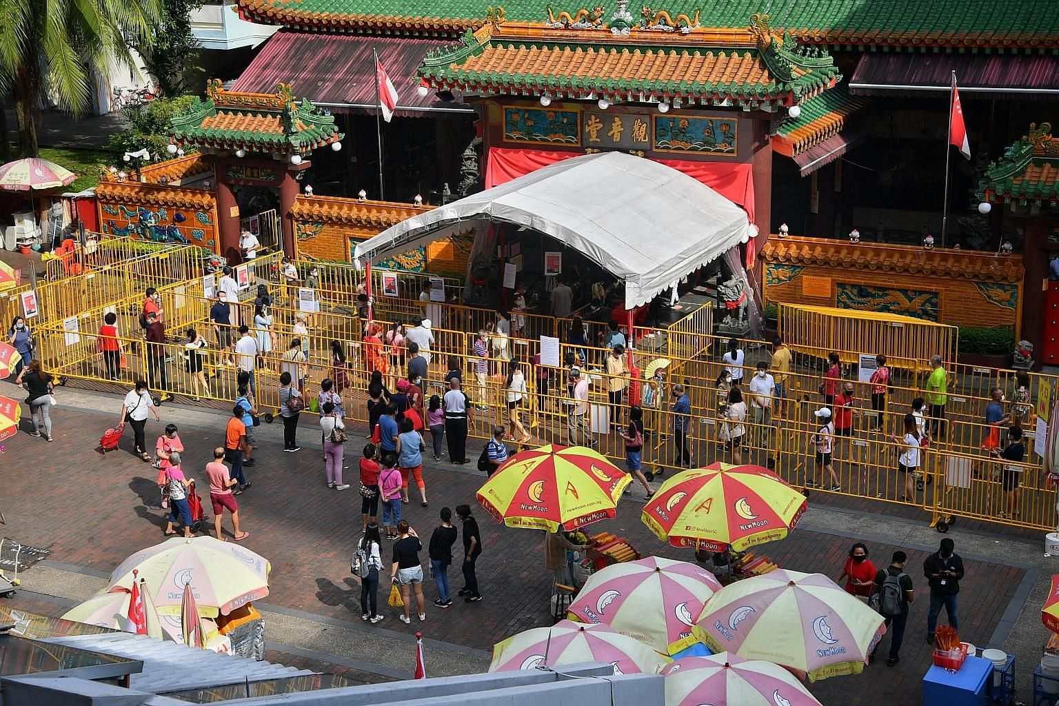 The Kwan Im Thong Hood Cho Temple reopened yesterday, four months after it closed amid the coronavirus pandemic. Devotees were seen observing safe distancing (above and far right) as they queued to enter the temple to offer their prayers. The long li