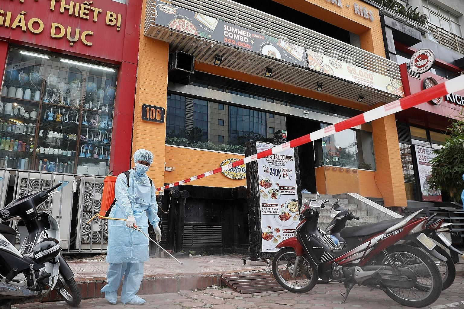 A worker spraying disinfectant outside a pizza parlour in Hanoi where a worker tested positive for Covid-19 after returning from Danang. Apart from the capital, Vietnam's new infections are in Danang, Ho Chi Minh City and Dak Lak province in the cent