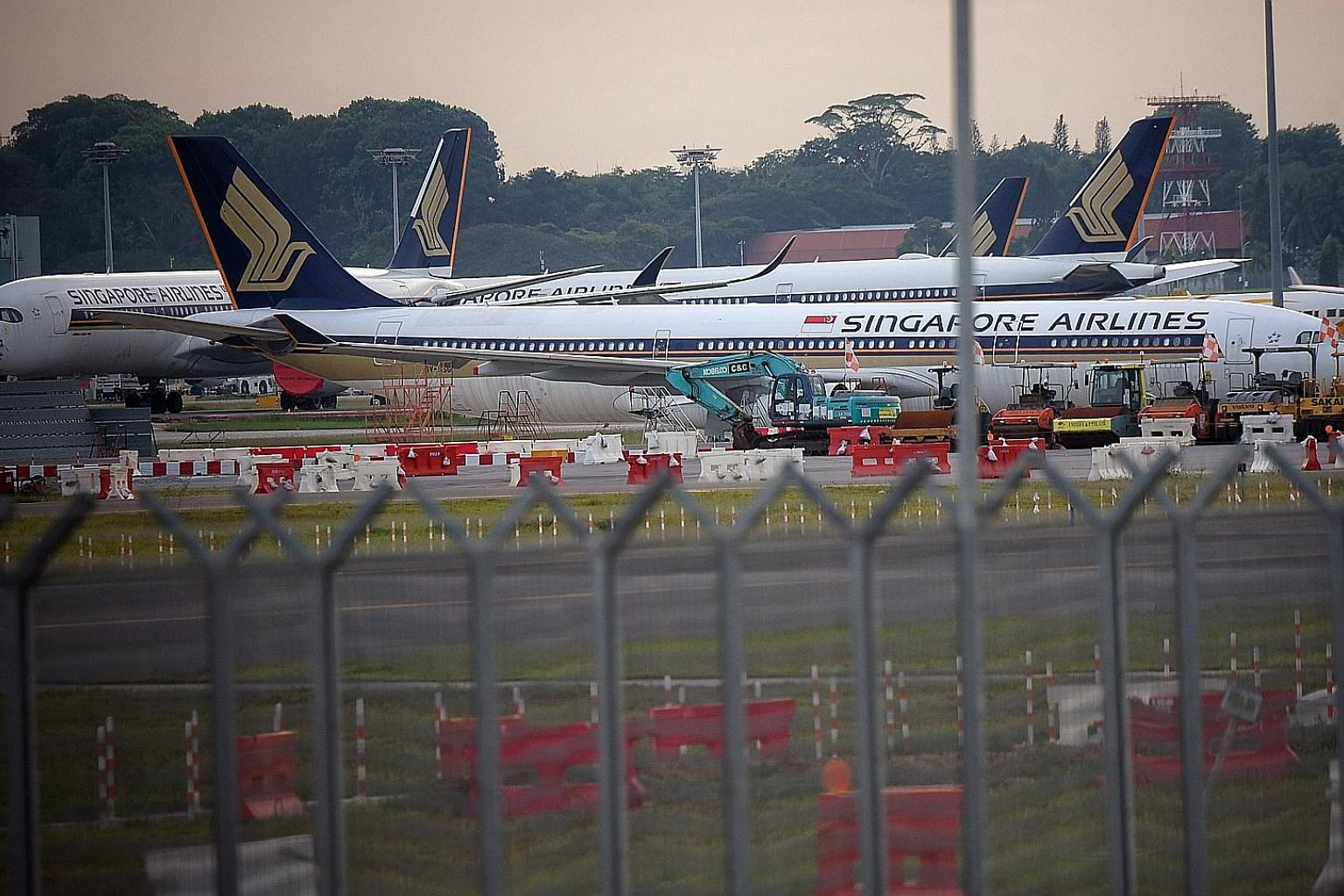 Singapore Airlines planes parked on the tarmac of Changi Airport last month as air travel demand evaporated amid travel restrictions and border controls imposed around the world to contain the spread of the coronavirus.