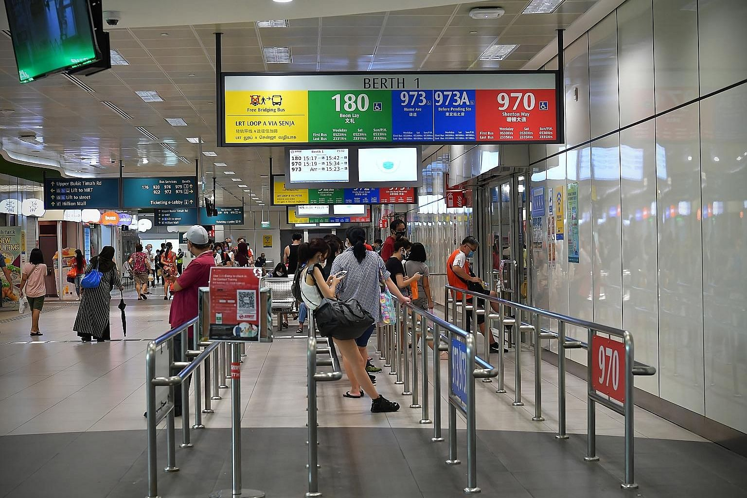 Commuters waiting for buses at the Bukit Panjang Integrated Transport Hub yesterday. Tests showed that the four new cases were likely to have had past infections and are no longer infectious. The two bus drivers and two interchange staff were last at