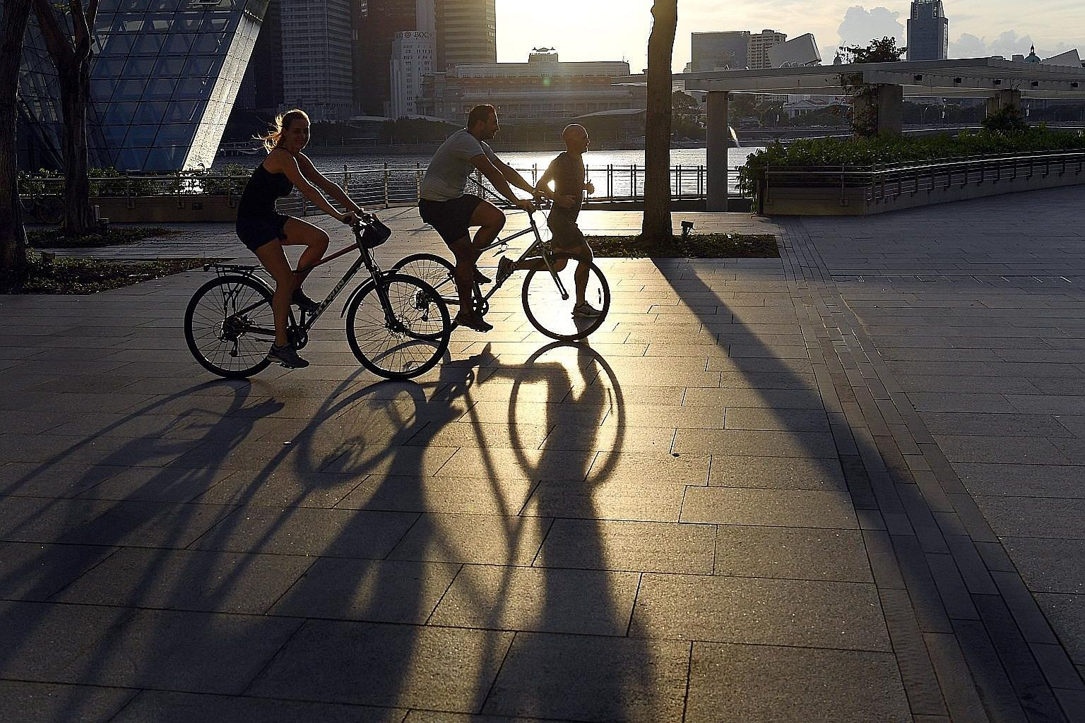 Cyclists and a jogger at the Marina Bay Waterfront Promenade in April. Exercise is more beneficial for those with a diet low in sugar and saturated fat.
