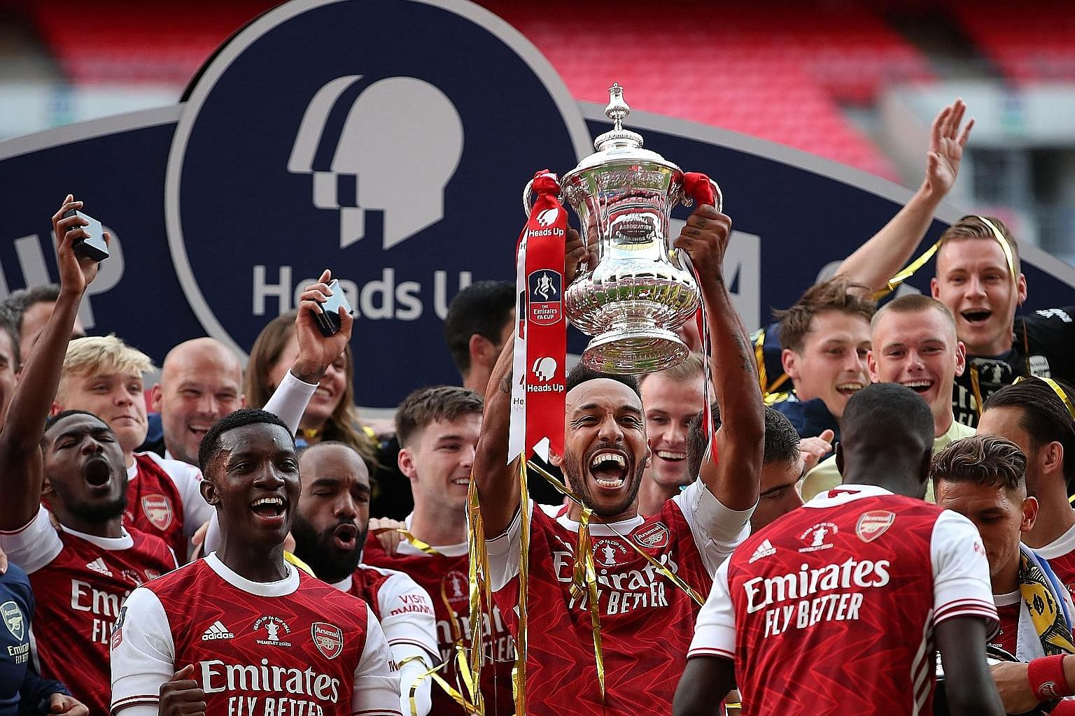 Above: Pierre-Emerick Aubameyang beats Chelsea goalkeeper Willy Caballero to give Arsenal a 2-1 lead at Wembley Stadium, which they held on to win. Left: Gabonese striker and captain Aubameyang holding the trophy as the Gunners celebrate their record