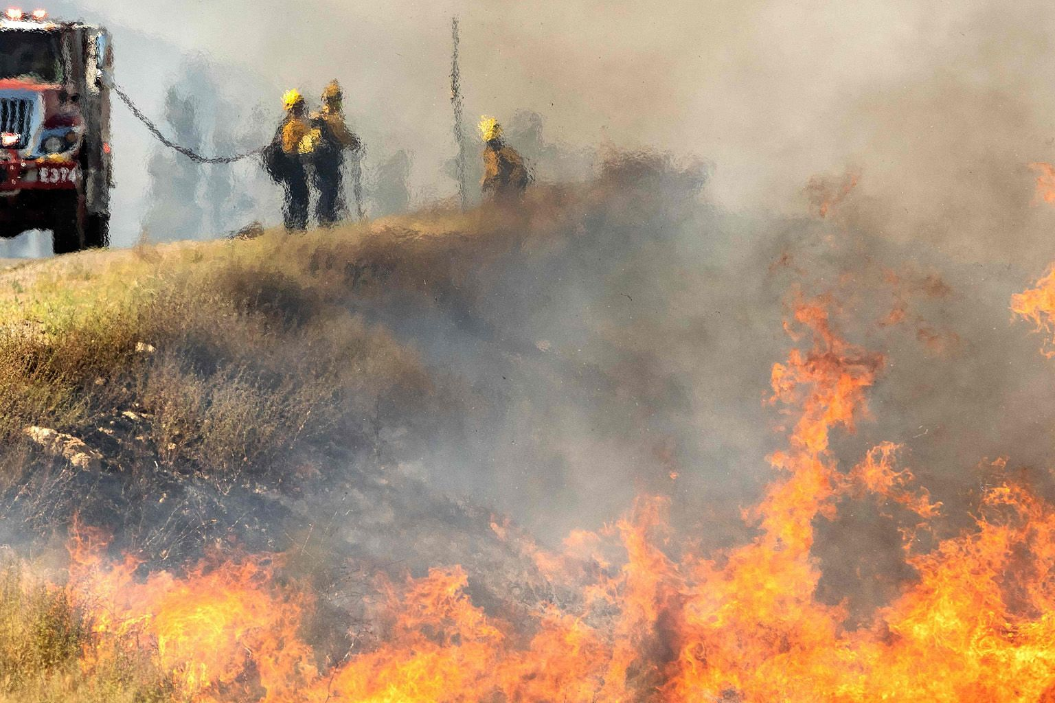 Firefighters, seen through heat from flames, battling the wildfire near Banning, in Southern California, last Saturday. PHOTO: AGENCE FRANCE-PRESSE