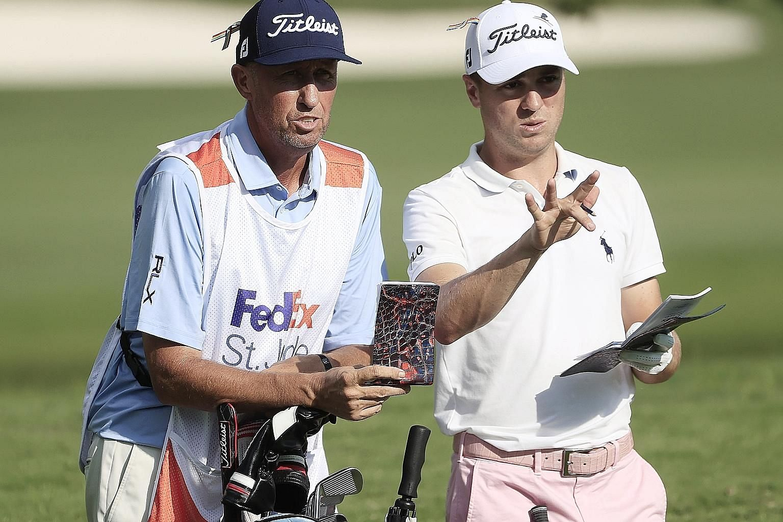 """Justin Thomas and caddie Jim """"Bones"""" Mackay discussing his second shot on the par-four final hole on Sunday. He saved par with a """"pretty sick"""" chip for a three-shot win in the WGC event in Memphis."""
