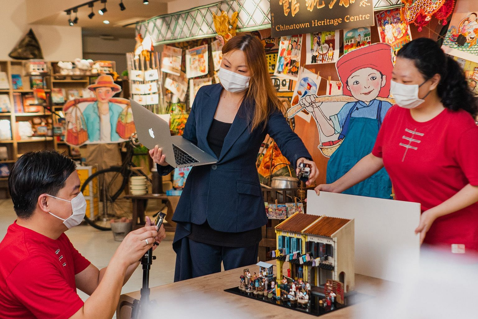 Chinatown Heritage Centre director Margaret Zhang and her team taking product photos for the centre's e-shop, which was launched on June 29 after the team attended a United Overseas Bank workshop advising small and medium-sized enterprises on how to