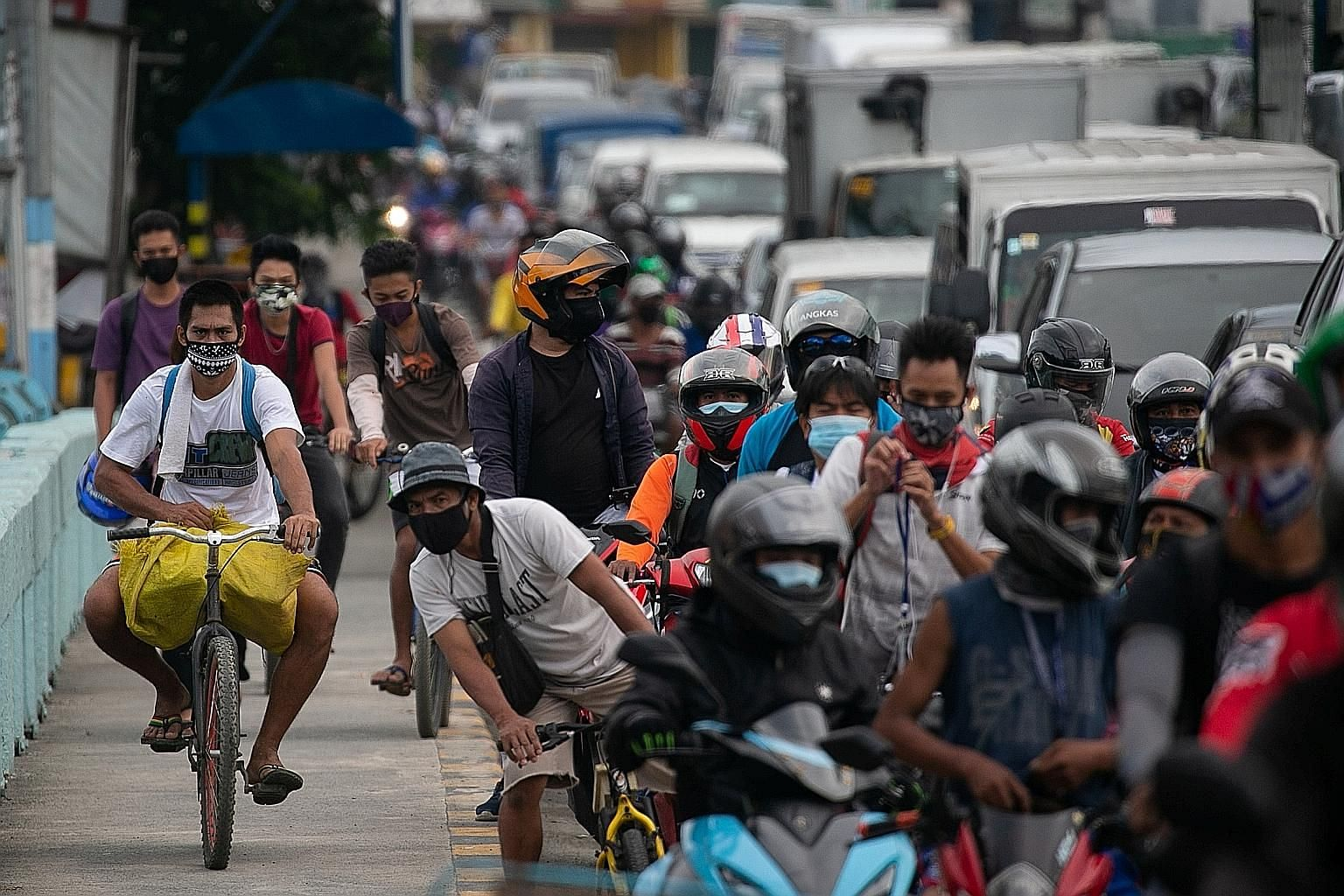 Cyclists riding on the sidewalk as traffic built up at a checkpoint in Marikina city in Metro Manila yesterday, the first day of a stricter lockdown to curb coronavirus infections in the Philippines. PHOTO: REUTERS A Philippine soldier checking the d