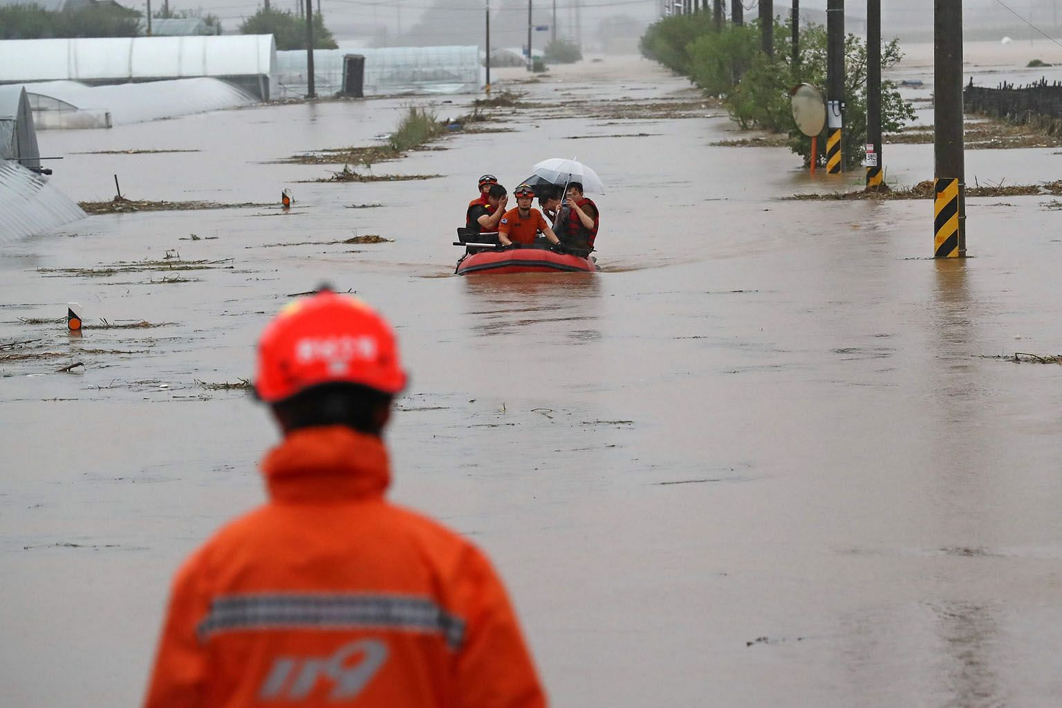 Big waves battering Shengsi county in eastern China's Zhejiang province yesterday as Hagupit, the fourth typhoon this year, struck. PHOTO: XINHUA Rescue workers in South Korea helping people cross a flooded field in a village near Cheonan on Monday.