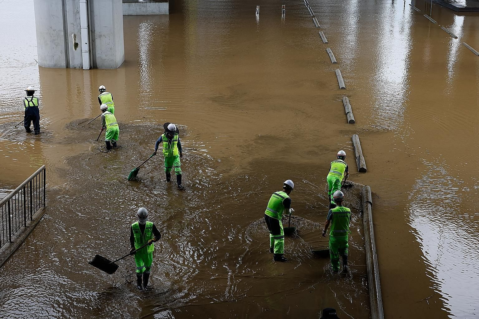 South Korean workers clearing mud from a flooded area under a bridge in Seoul on Tuesday after heavy rain triggered floods and landslides.
