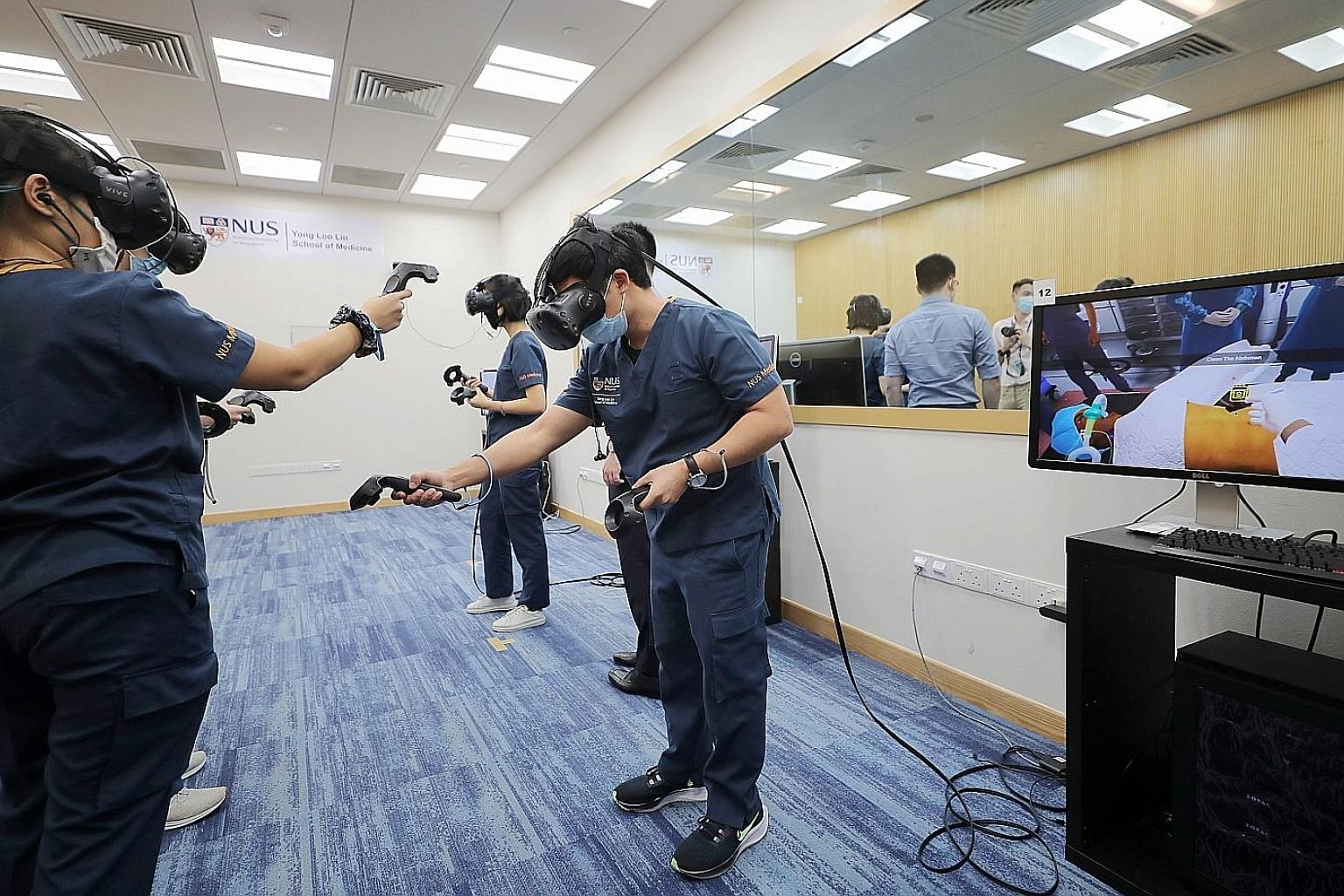 A group of third-year students at the NUS Yong Loo Lin School of Medicine learning in a virtual environment with the use of VR headsets and hand-held controllers. Their movements are observed by educators who guide them.