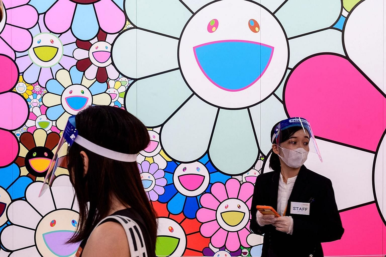 People wearing face shields next to Pop Up Flower, a work by artist Takashi Murakami, at a media preview of Stars: Six Contemporary Artists From Japan To The World at the Mori Art Museum in Tokyo last month.