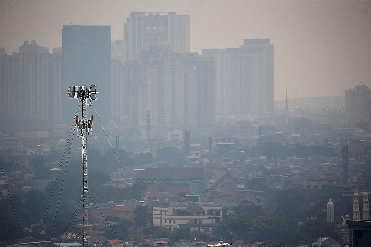 Smog over Jakarta on July 12. Extreme weather affecting the city has become more severe over the years, threatening food supply, worsening flooding and posing socio-economic risks such as disrupting school activities.