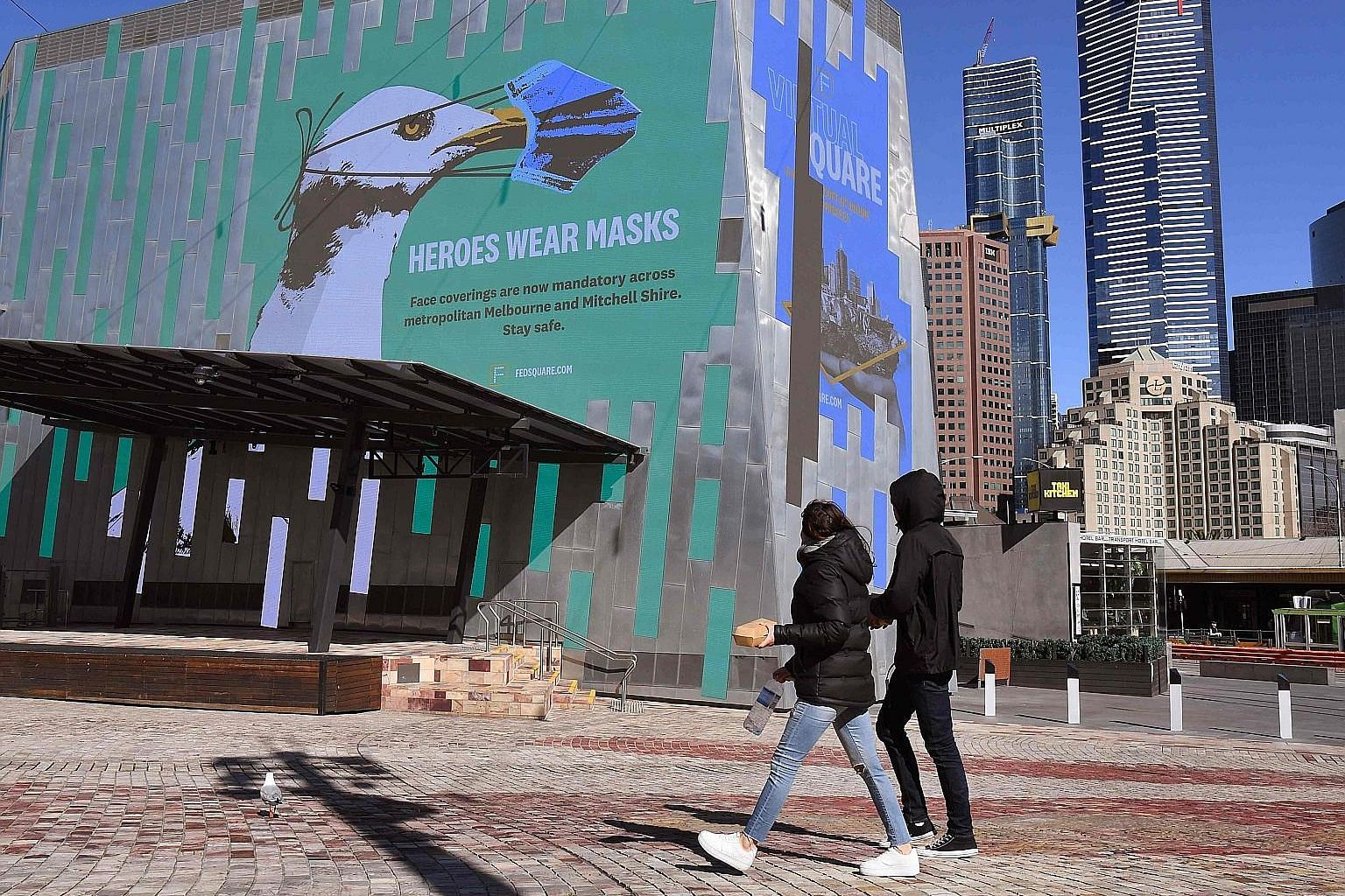 A mural in Melbourne's central business district urging people to wear a mask yesterday. Shops were shut and streets were deserted in the city of about five million people. Residents are still allowed to go out during the day for exercise and food, o