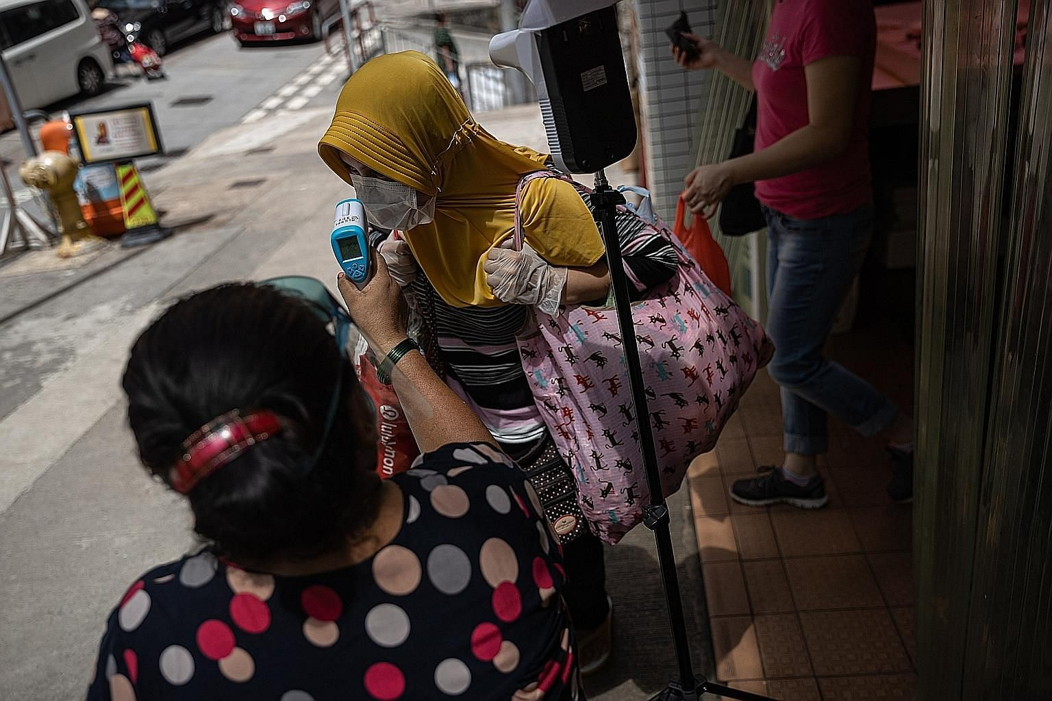A foreign domestic worker getting her temperature checked before entering a wet market in Hong Kong yesterday. The health authorities yesterday reported 89 new confirmed Covid-19 cases, bringing the total tally of cases in the city to 3,938. PHOTO: E