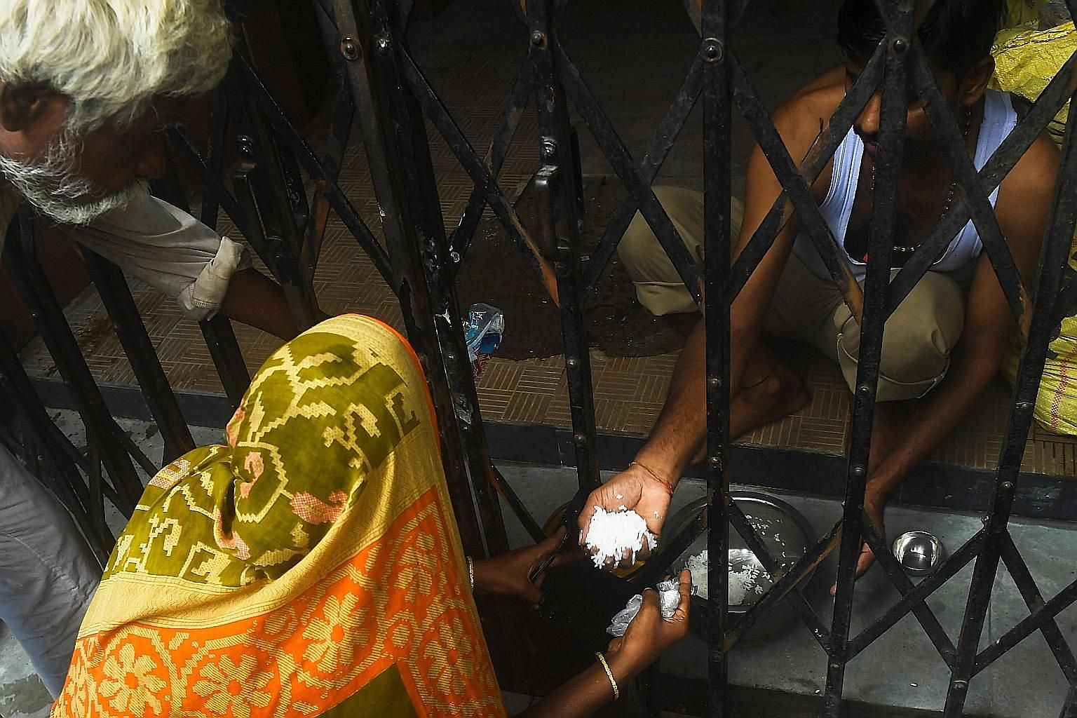 A man distributing food to homeless people in Kolkata, West Bengal, this week during a day-long lockdown imposed by the state government after a surge in coronavirus cases. PHOTO: AGENCE FRANCE-PRESSE