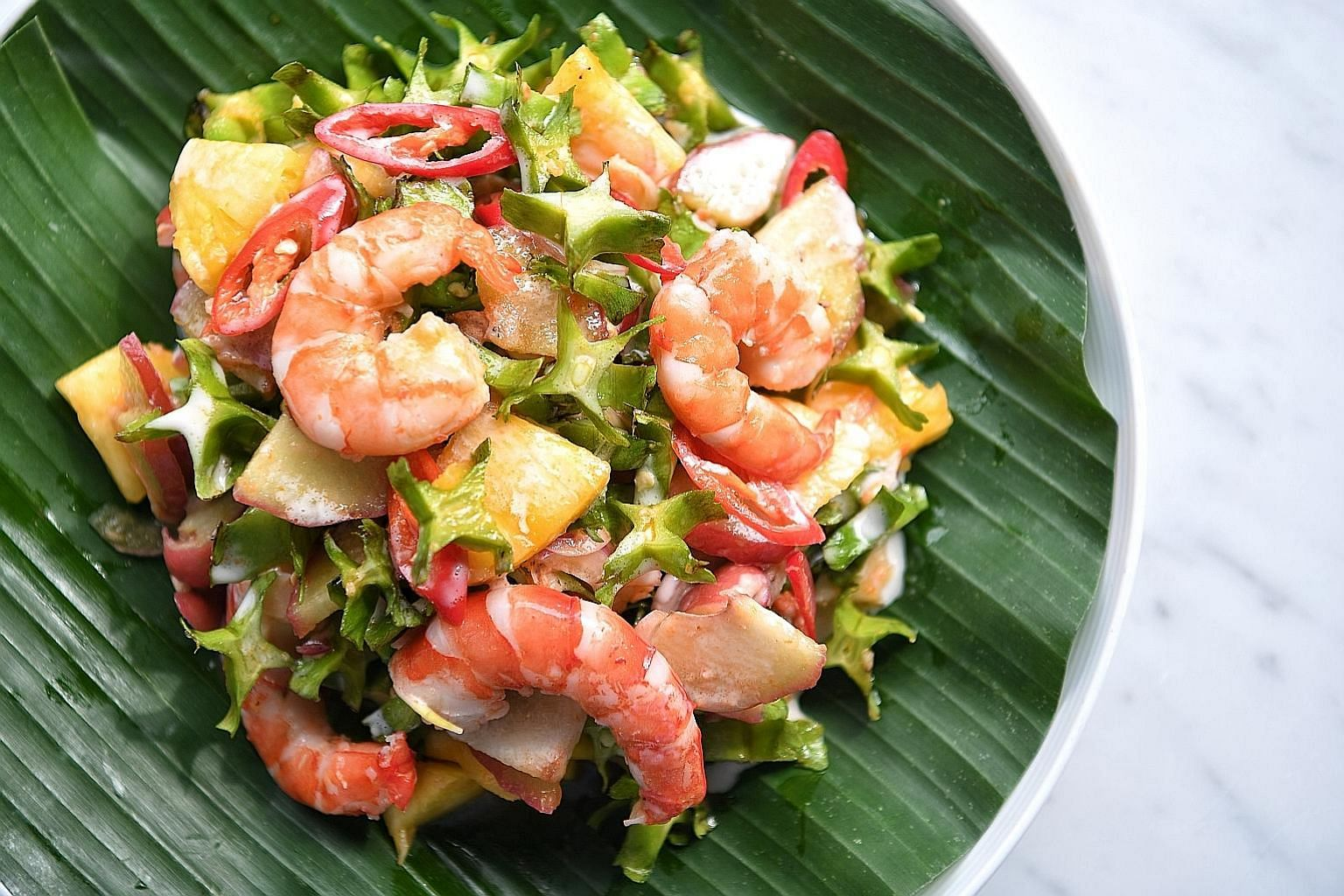 Chilli sauce (left) and cinchalok or fermented shrimp (right) add heat and umami to the salad dressing. A spicy yet refreshing prawn salad made with wing beans (below) as the base.