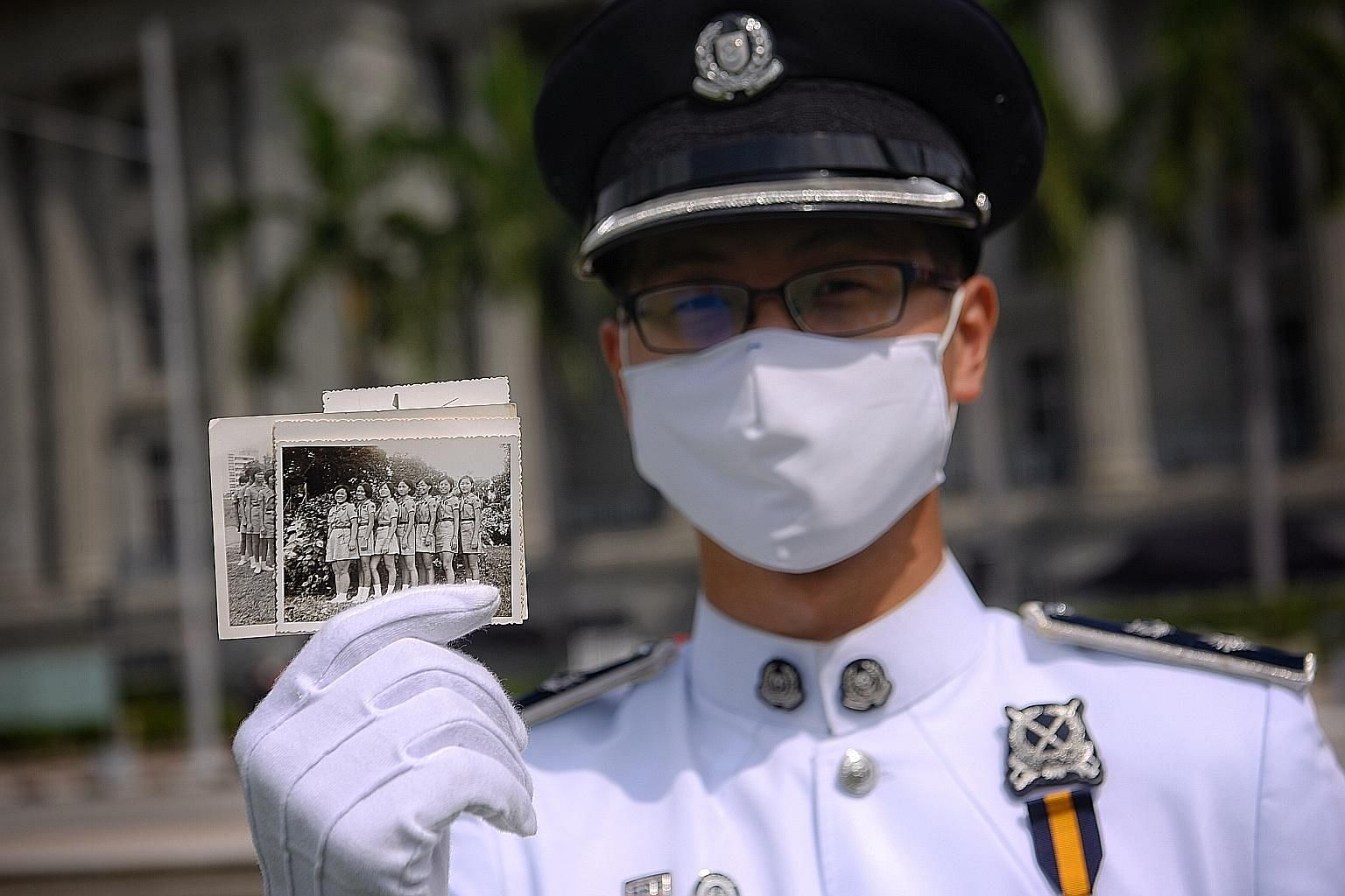DSP Lee Ting Wei, 29, commander of the Singapore Police Force guard-of-honour contingent, with an old picture of his mother (second from right) in the Girl Guides. She took part in the 1973 National Day Parade.