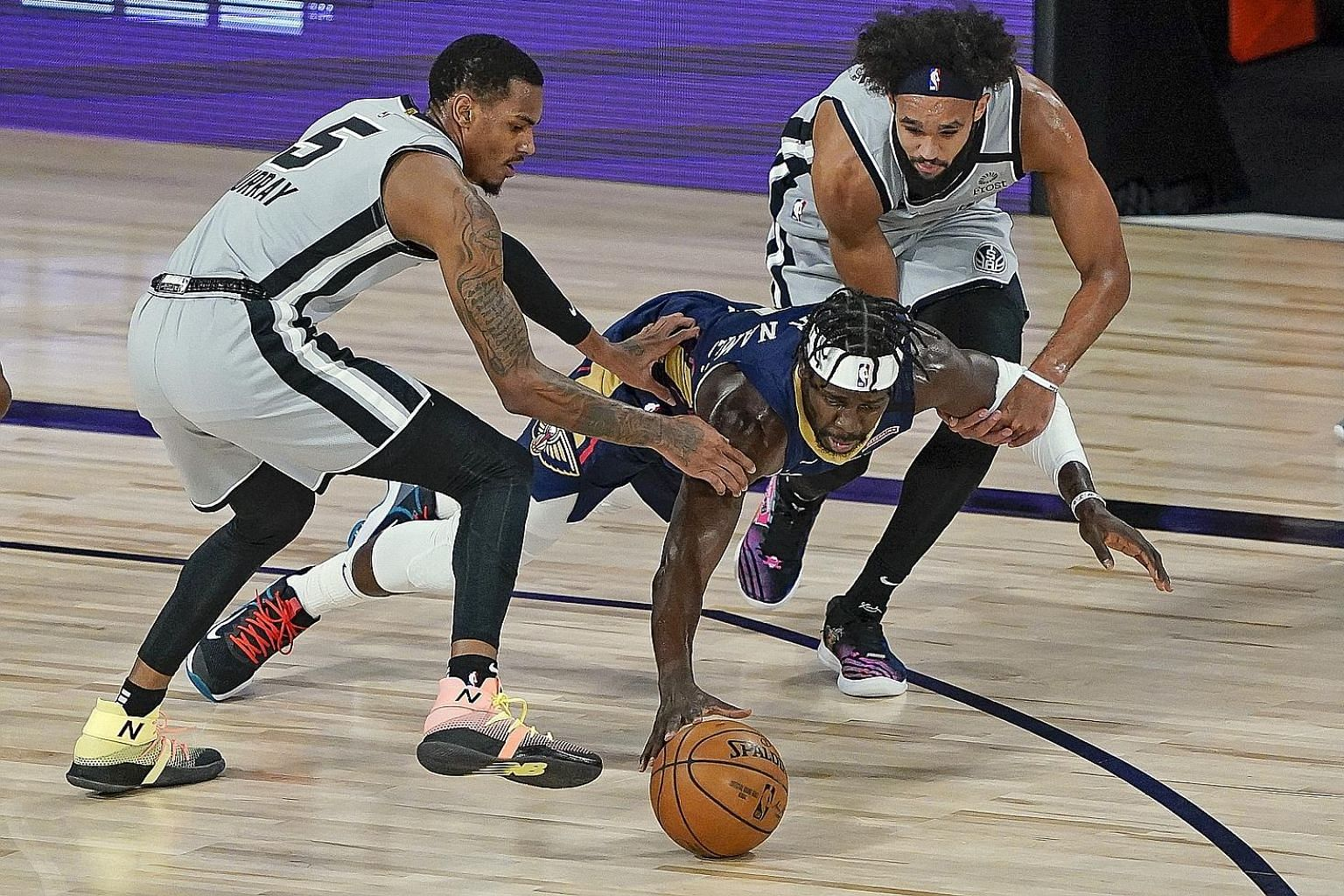 Pelicans guard Jrue Holiday diving for a loose ball between Spurs guards Dejounte Murray and Derrick White during their NBA game on Sunday. San Antonio won 122-113 to knock New Orleans out of play-off contention. There are two spots left with the Spu