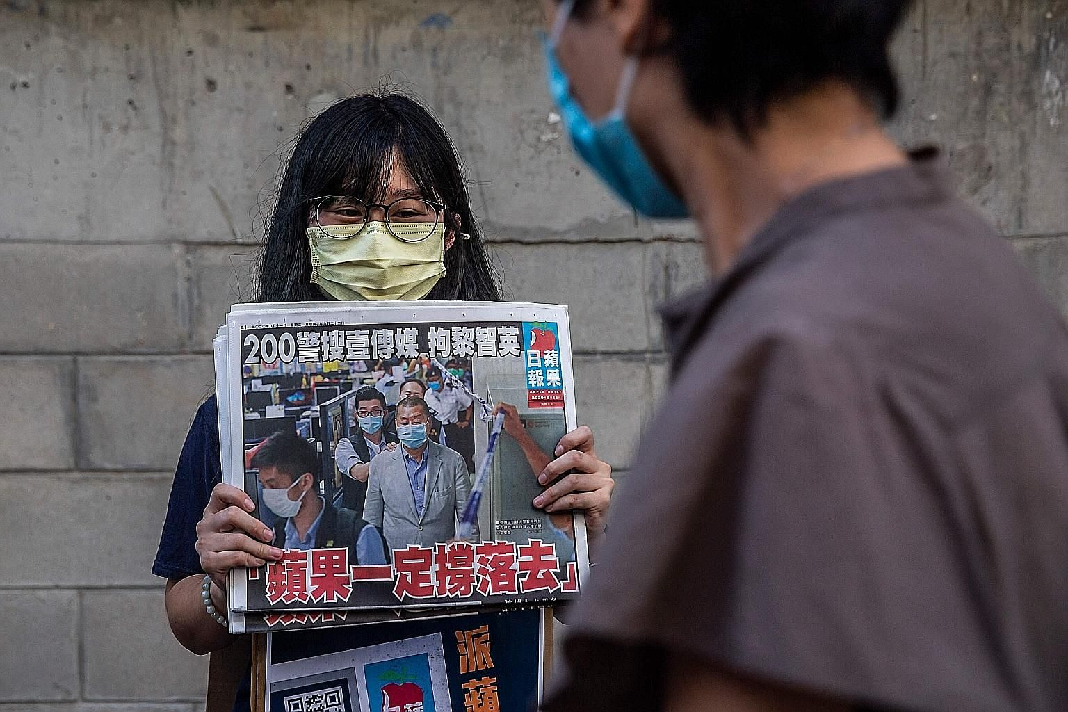 A volunteer distributing copies of the Apple Daily newspaper in Hong Kong yesterday. The newspaper's front page depicts owner Jimmy Lai being detained by police officers a day earlier. His arrest comes amid a crackdown on the pro-democracy opposition