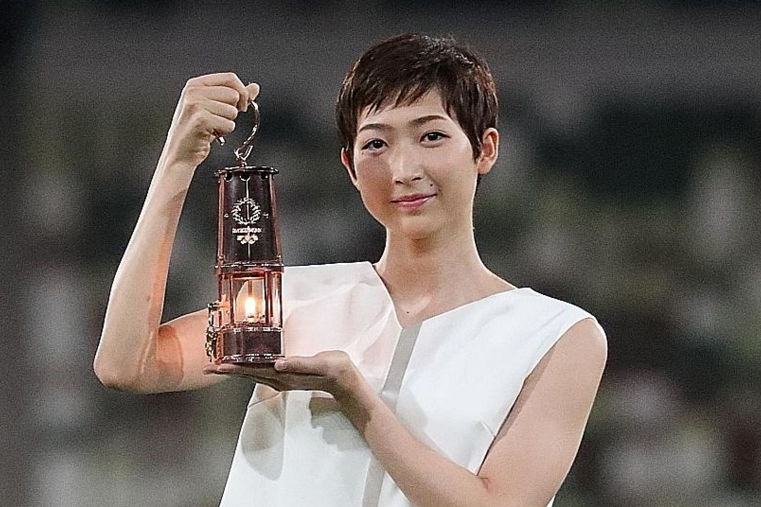 "Japanese swimming star Rikako Ikee with the lantern containing the flame, during the unveiling of the ""One Step Forward +1 Message"" at the Tokyo Olympic Stadium on July 23 that marked a year to the postponed Games."