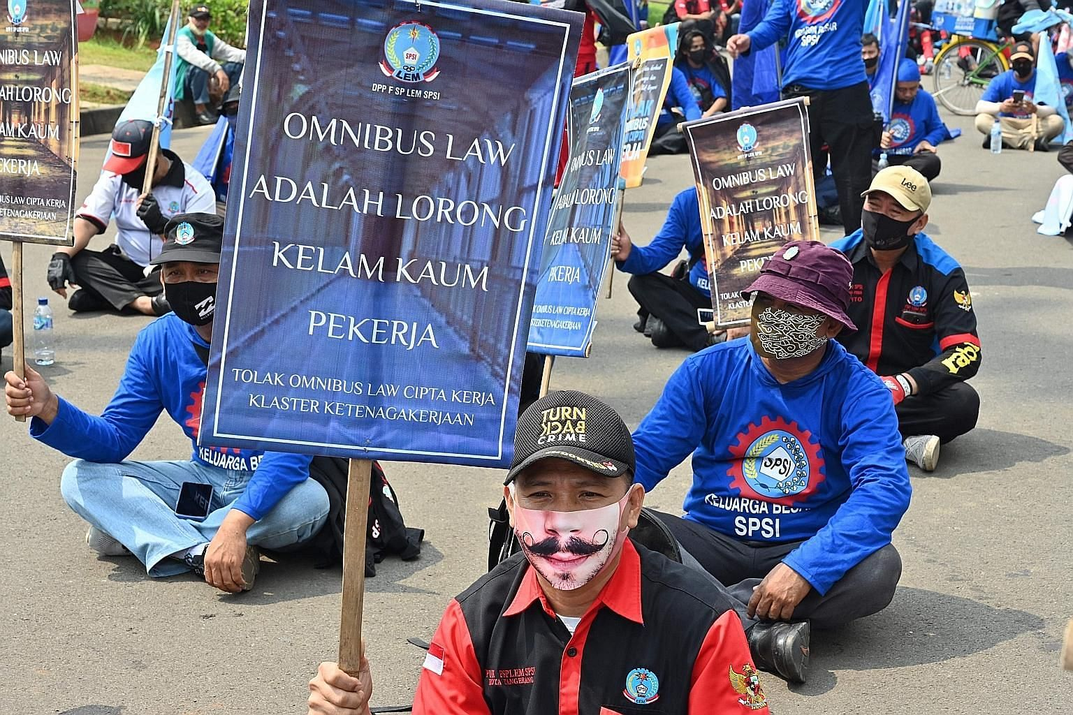 Indonesian workers protesting outside the presidential palace in Jakarta on July 22 against the Bill on job creation they believe will deprive workers of their rights. The Bill will allow employers to hire and fire with lower severance pay and benefi
