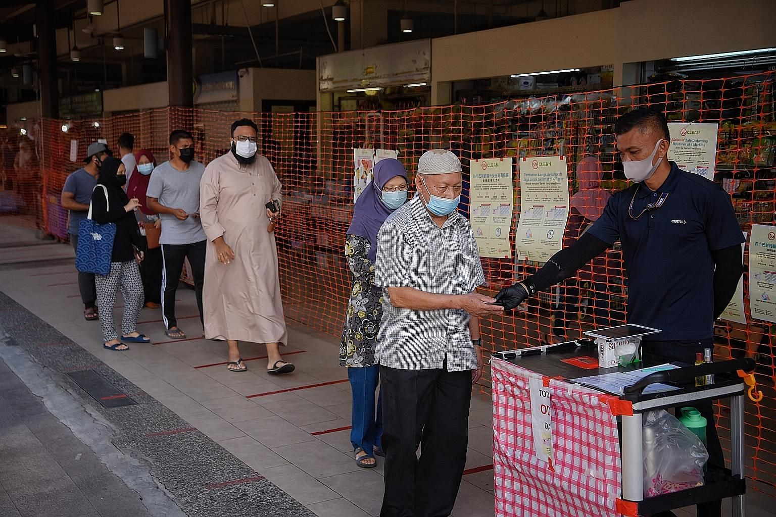 Shoppers getting their NRICs scanned at Geylang Serai Market. Currently, people can visit this market - and three others - only on alternate days, depending on the last digit of their NRIC number, but this rule will be lifted on weekdays from tomorro
