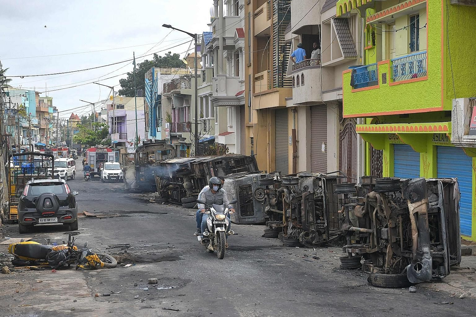Burnt police vehicles littered the street in Bengaluru yesterday following violence that broke out overnight after a Facebook post about the Prophet Muhammad sparked riots. Unable to quell protesters with batons and tear gas, officers opened fire as