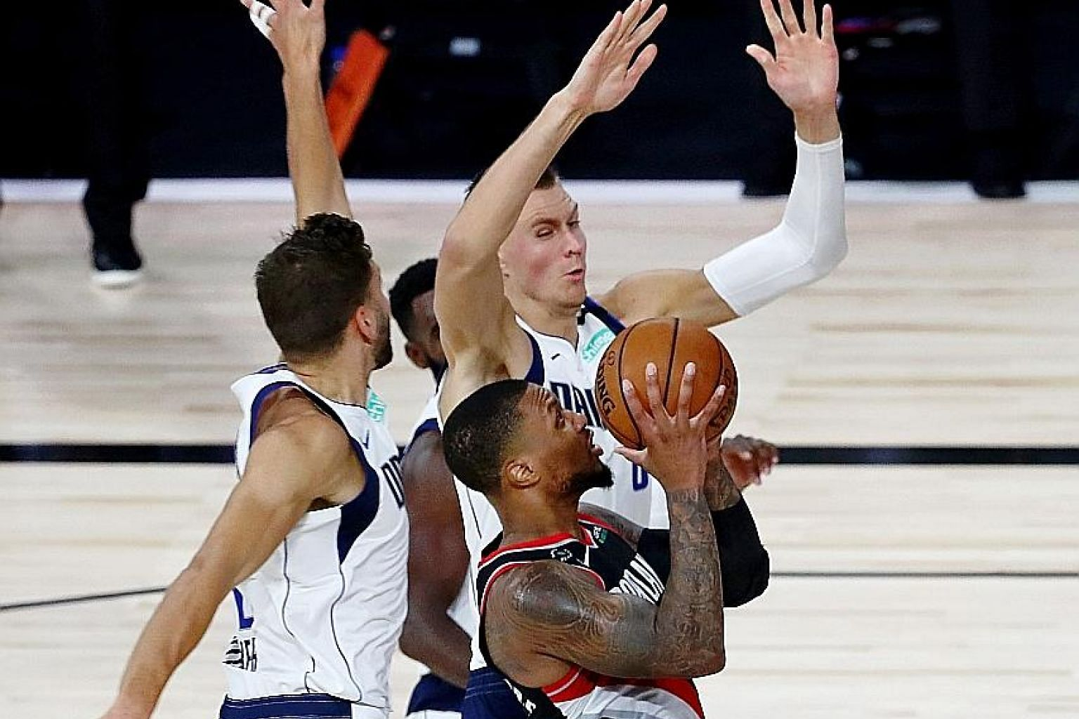 Portland guard Damian Lillard going for a shot despite the close attention of Dallas forward Maxi Kleber (left) and other players. The Blazers won 134-131.