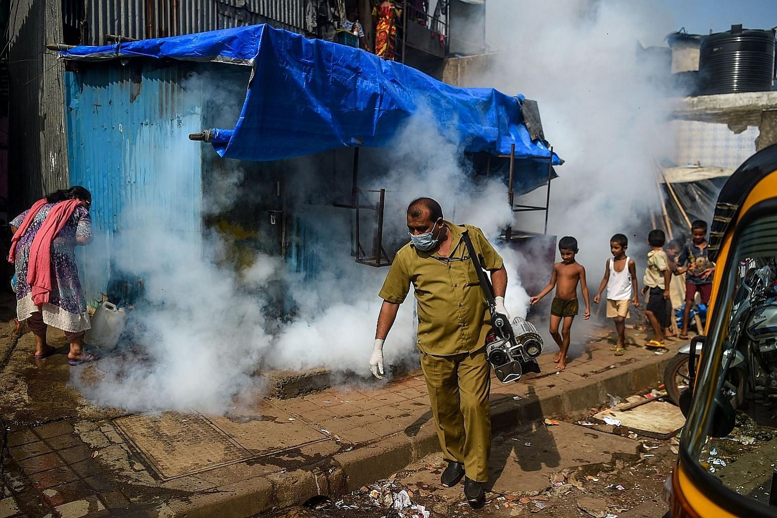 A patient using a balloon to strengthen her lungs as she recovered from Covid-19 at a makeshift hospital in Mexico City in June. A slum area being fumigated as a preventive measure against malaria and dengue in Mumbai, India. Lockdowns and supply-cha