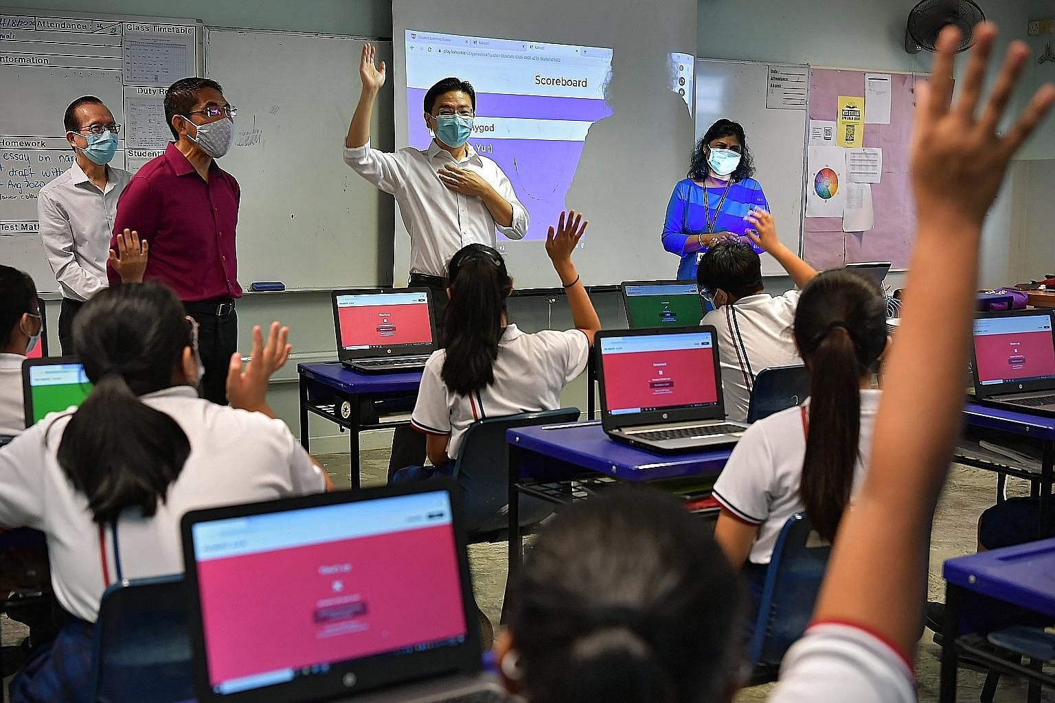 """Education Minister Lawrence Wong (centre) and Second Minister for Education Maliki Osman (second from left) at Marsiling Secondary School yesterday. Mr Wong said making education a social leveller will involve ensuring schools """"remain an uplifting fo"""