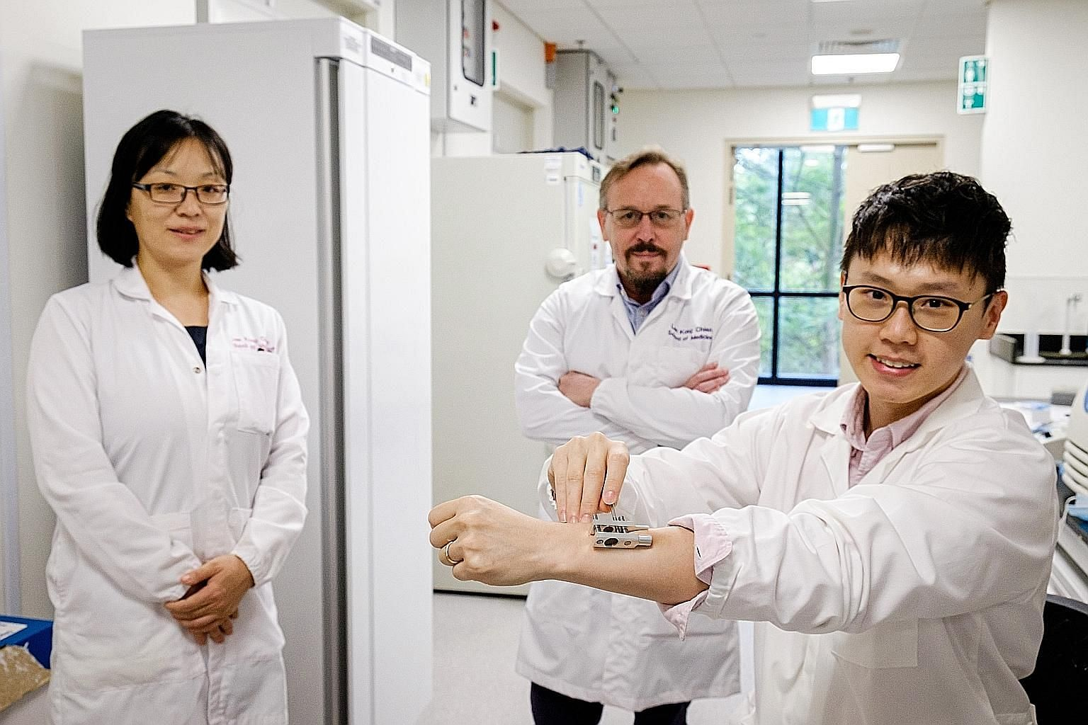 A*Star's Dr Daniel Lio (right) demonstrating his team's prototype device that uses two magnets to create temporary micropores to administer drugs more efficiently through the skin. With him are team members Wang Xiaomeng and David Laurence Becker of