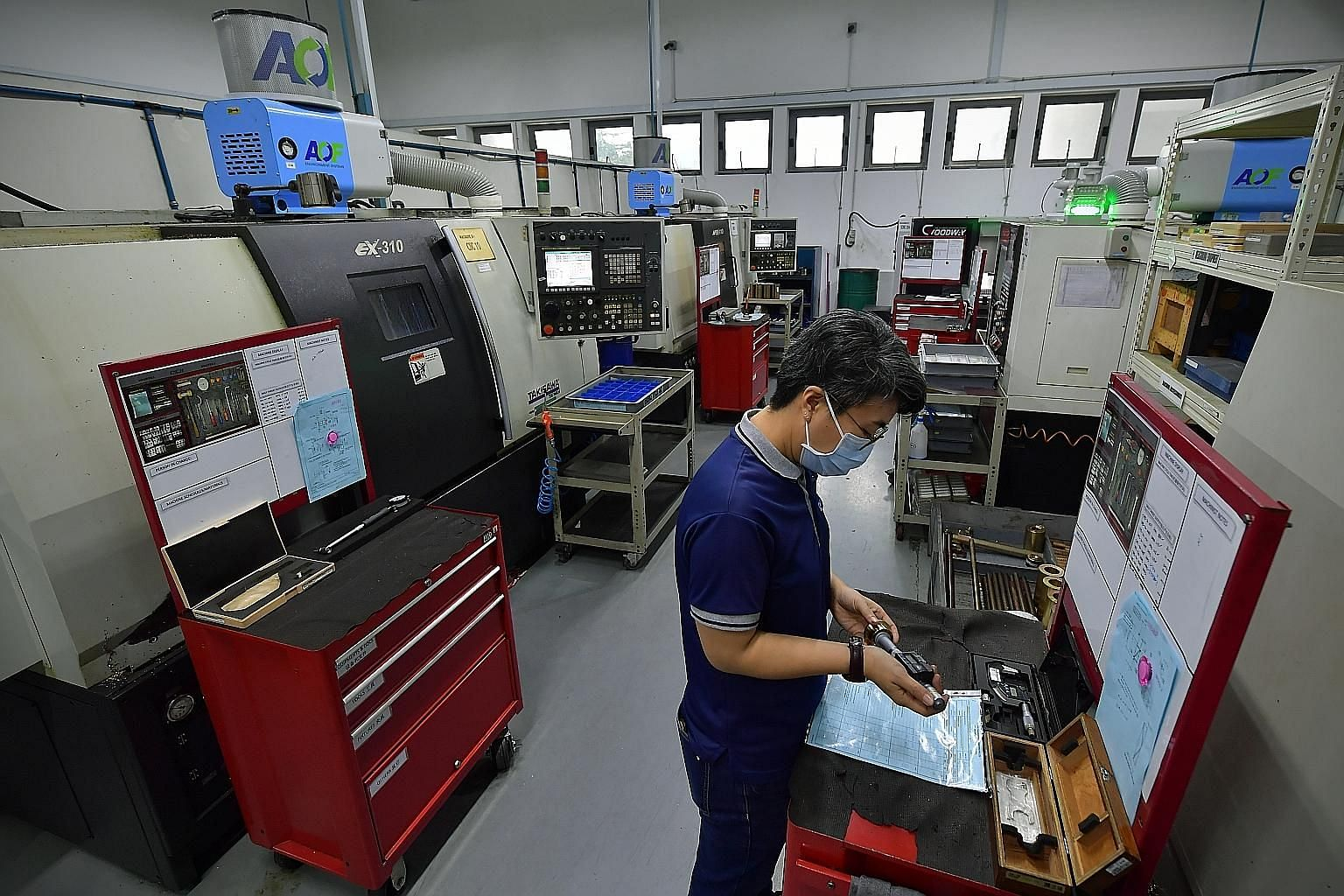 A computer numerical control machinist at Coway Engineering & Marketing inspecting a part produced by the company. The precision engineering firm has had to diversify beyond the aerospace and oil and gas sectors for business since the coronavirus pan