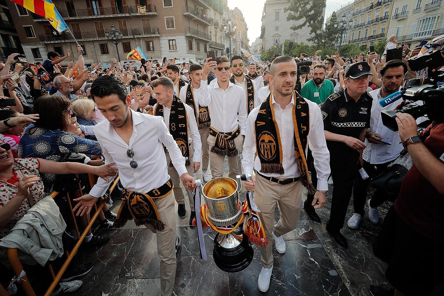 Above: Dani Parejo, Valencia's former captain who was sold to Villarreal, and Jaume Domenech carrying the Spanish King's Cup - the club's first trophy in 11 years - during celebrations in May last year. Below: Ferran Torres, taking on Real Madrid's F