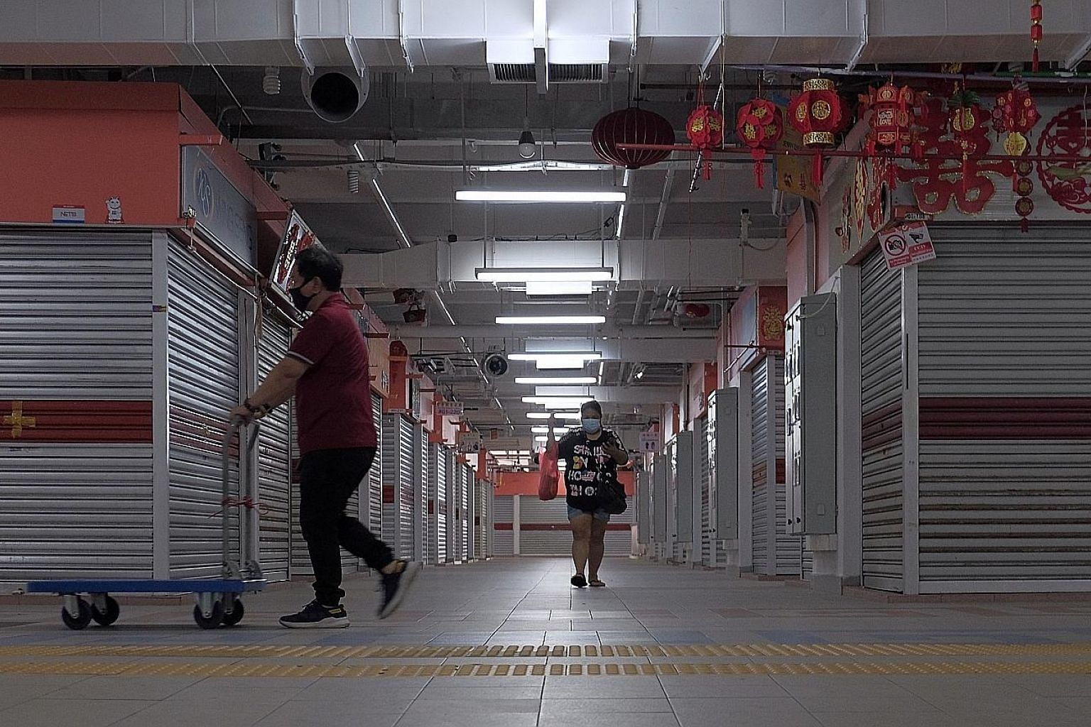 Shuttered shops in Chinatown Complex in April, two days after the circuit breaker started. Some sectors, including retail and food services, will get a flat 30 per cent wage subsidy for seven more months.