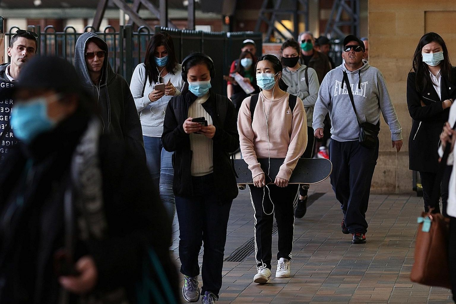 Commuters at Central Station in Sydney last week. The World Health Organisation said that many young people are unaware that they have been infected and are spreading the disease. One reason is that they may not see obvious symptoms that push them to