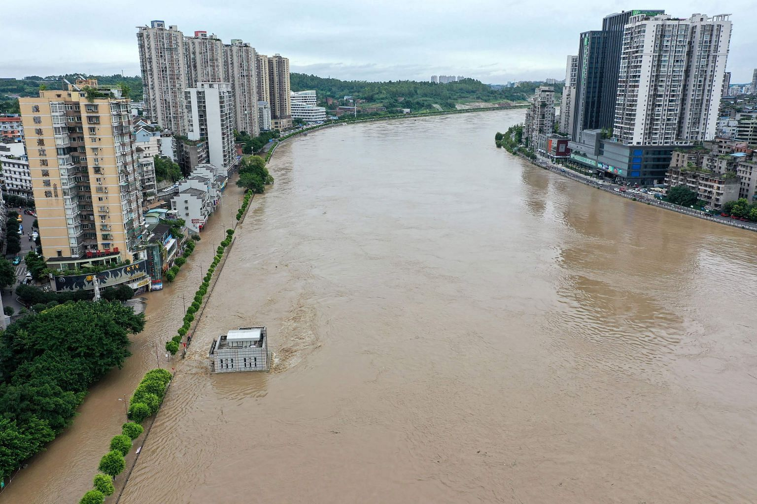 A swollen Tuojiang River yesterday, following heavy rain in south-western Sichuan province. Heavy rain lashed 27 out of 31 of the country's provinces since June this year. PHOTO: AGENCE FRANCE-PRESSE
