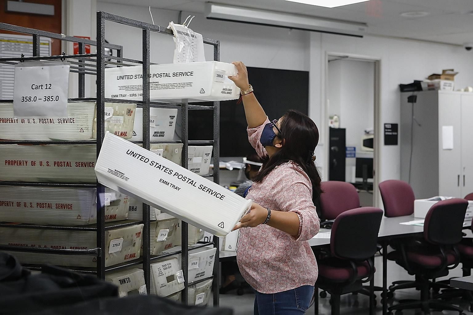 A worker holding US Postal Service bins with mail-in ballots in Florida on Tuesday, amid concerns that the agency's chief is hampering its ability to handle voting by mail. PHOTO: BLOOMBERG