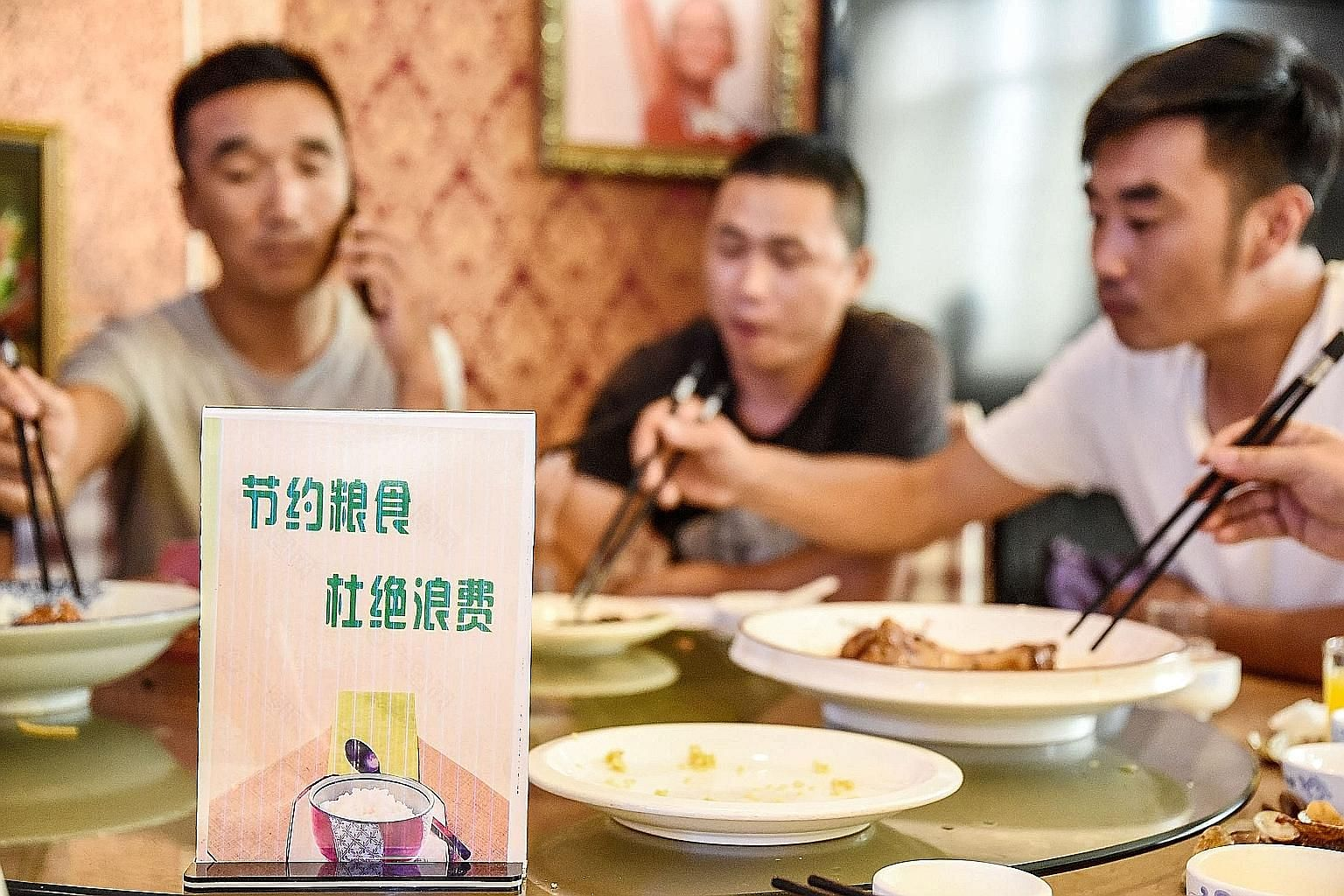 A sign encouraging people not to waste food displayed at a restaurant in Handan, Hebei province, last week. The average Chinese diner throws away 93g of food per meal when eating out, according to a study. This is about 11.7 per cent of his meal. PHO