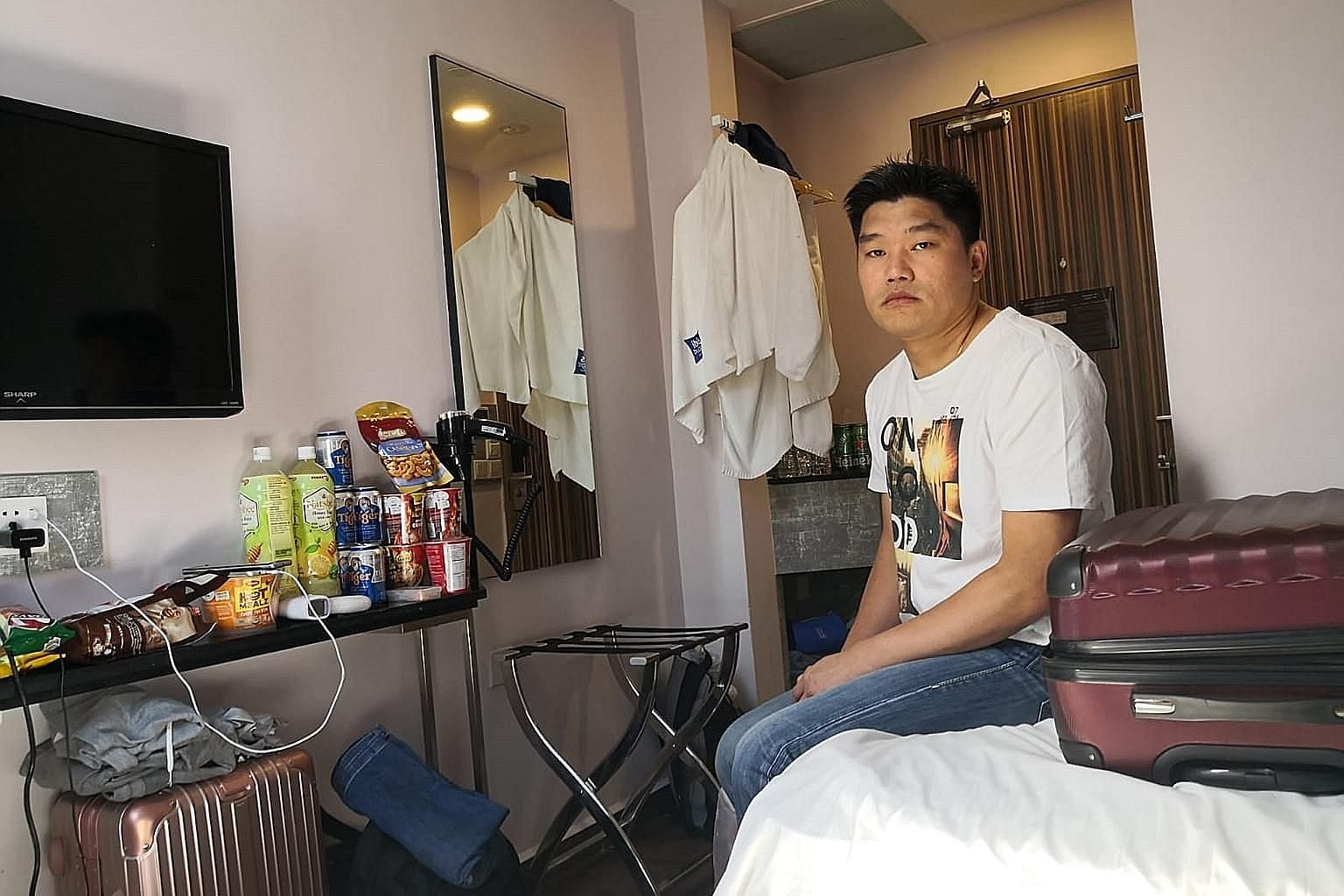 """Mr Eddie Chow, seen below in a video call with his family, said his wife """"is being left alone to take care of our eight-month-old son and five-year-old daughter"""". PHOTOS: GAIN CITY"""