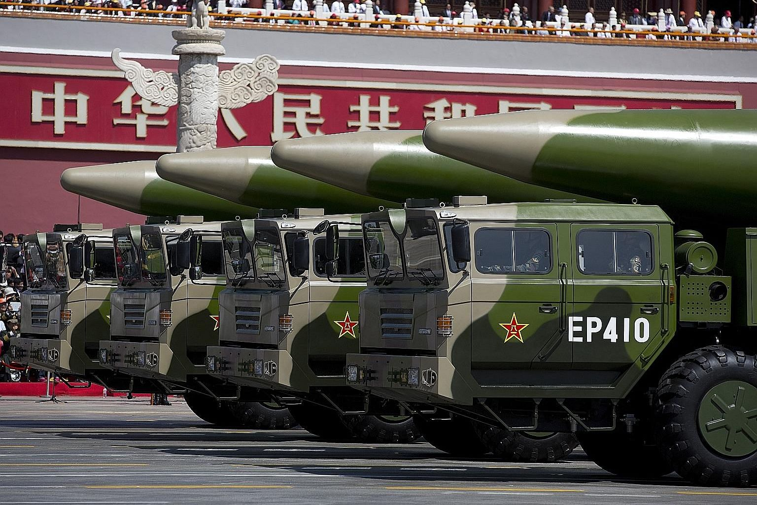 Left: Military vehicles carrying ballistic missiles at a Beijing parade in 2015. Above: An Aug 18 image reportedly showing a Chinese submarine entering an underground base at Hainan island on the South China Sea. PHOTOS: AGENCE FRANCE-PRESSE