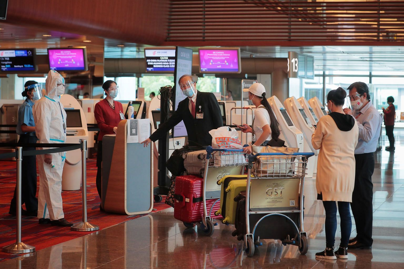 Ms Tang Yun (in cap) and Ms Zhang Yan (right) checking in at Changi Airport yesterday. They were among the first batch of China-bound passengers leaving Changi Airport yesterday after stricter rules were imposed.