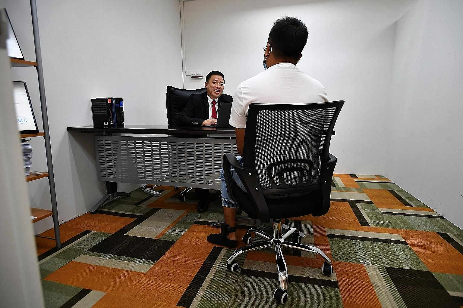 Lawyer Peter Ong Lip Cheng speaking to his client - who is wearing an electronic tag on his left ankle - at his office on Thursday. The rise in the number of accused persons who are released on reduced bail with e-tagging, as well as those placed on