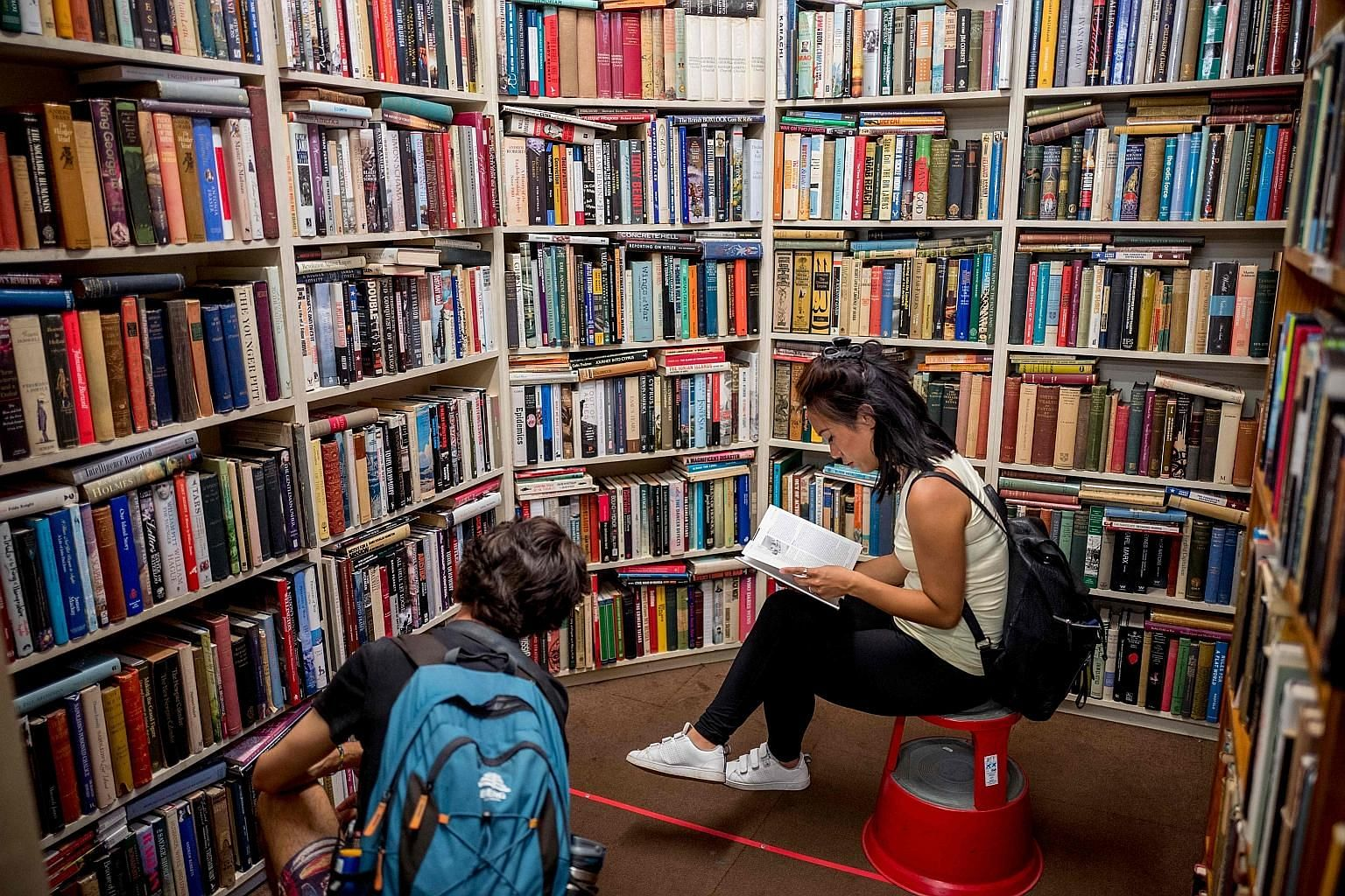 Customers in a second-hand bookshop in London in June. The threat to physical books looms as printing companies run into financial trouble and the supply of publication paper falls.