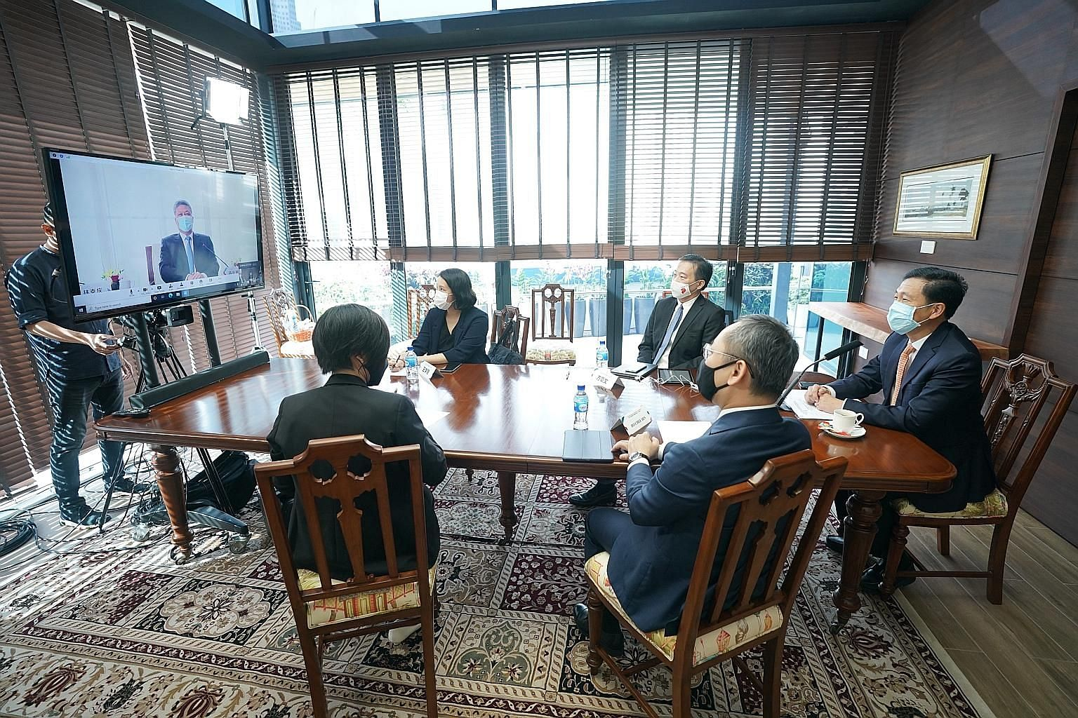 Guangdong Governor Ma Xingrui (on screen) with Singapore Transport Minister Ong Ye Kung (right), Enterprise Singapore chief executive Png Cheong Boon (on Mr Ong's right) and delegates from Enterprise Singapore and the Ministry of Trade and Industry a