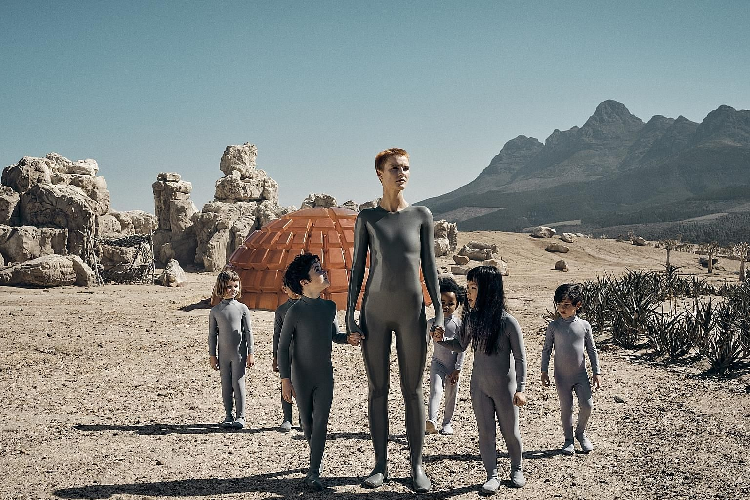 Science-fiction series Raised By Wolves, directed by Ridley Scott (above), stars Amanda Collin (left, centre) as an android raising human children on an inhospitable planet.
