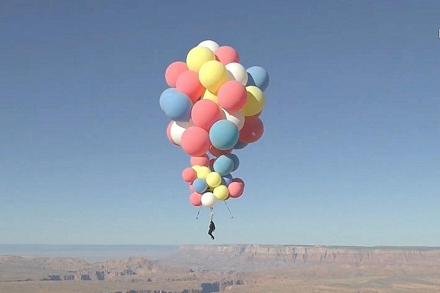 Extreme performer David Blaine flying over the desert in Page, Arizona, on Wednesday, aided by a parachute and a cluster of balloons.