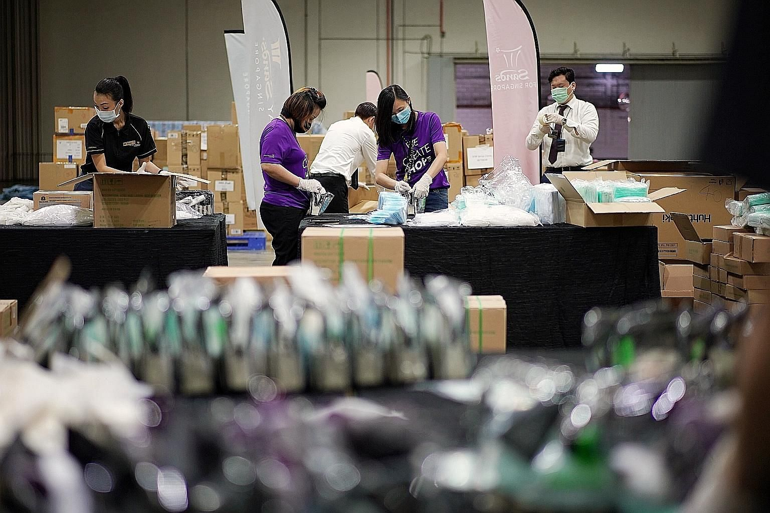 Marina Bay Sands (MBS) staff packing care kits yesterday at one of the halls in Sands Expo and Convention Centre. More than 300 MBS staff from more than 40 departments - including (from far left) assistant manager Veronica Lim, 33, senior administrat