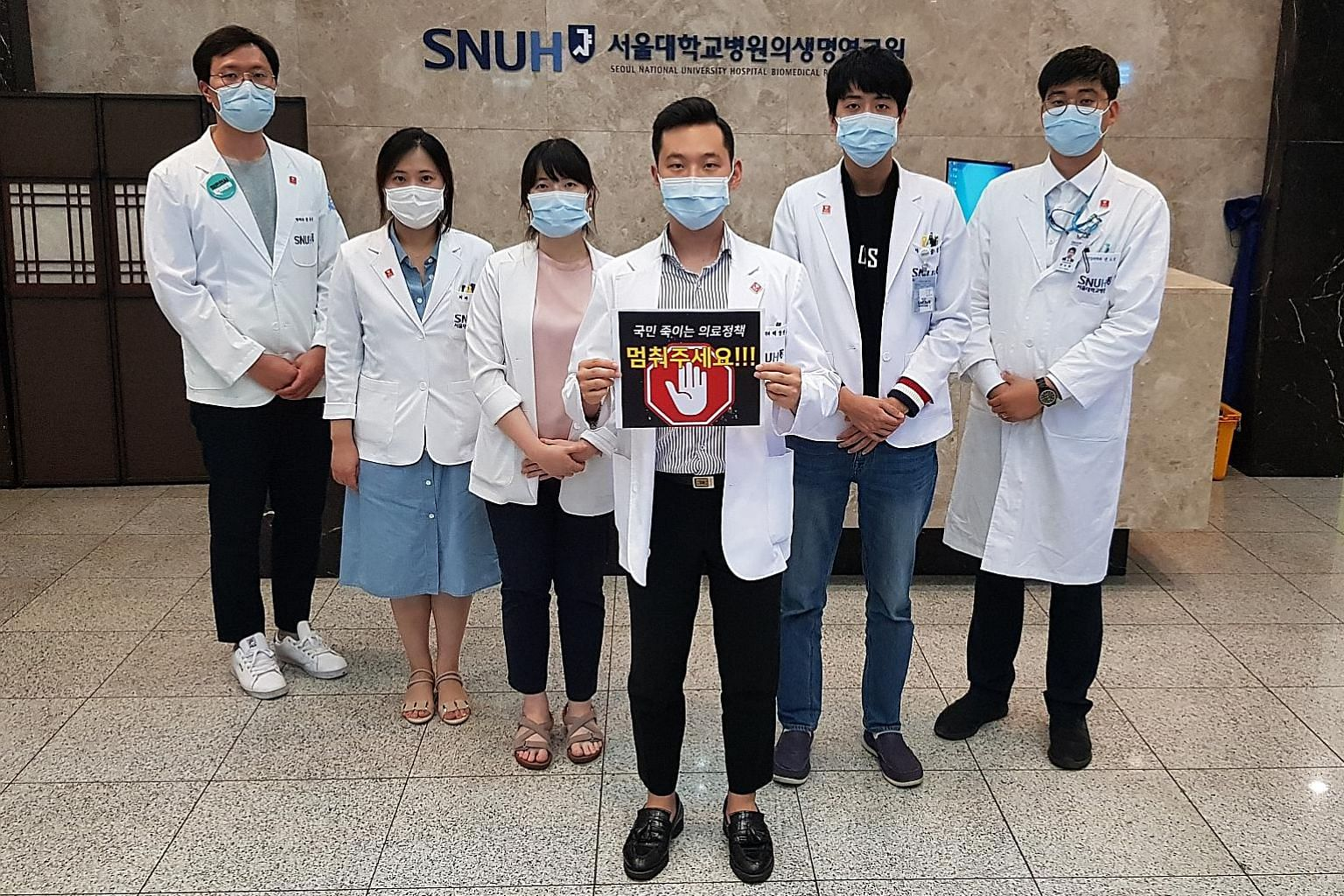 "A group of resident doctors at Seoul National University Hospital who joined a strike against the government's medical reform plan, holding a sign that says ""stop medical policies that kill people"". ST PHOTO: CHANG MAY CHOON"