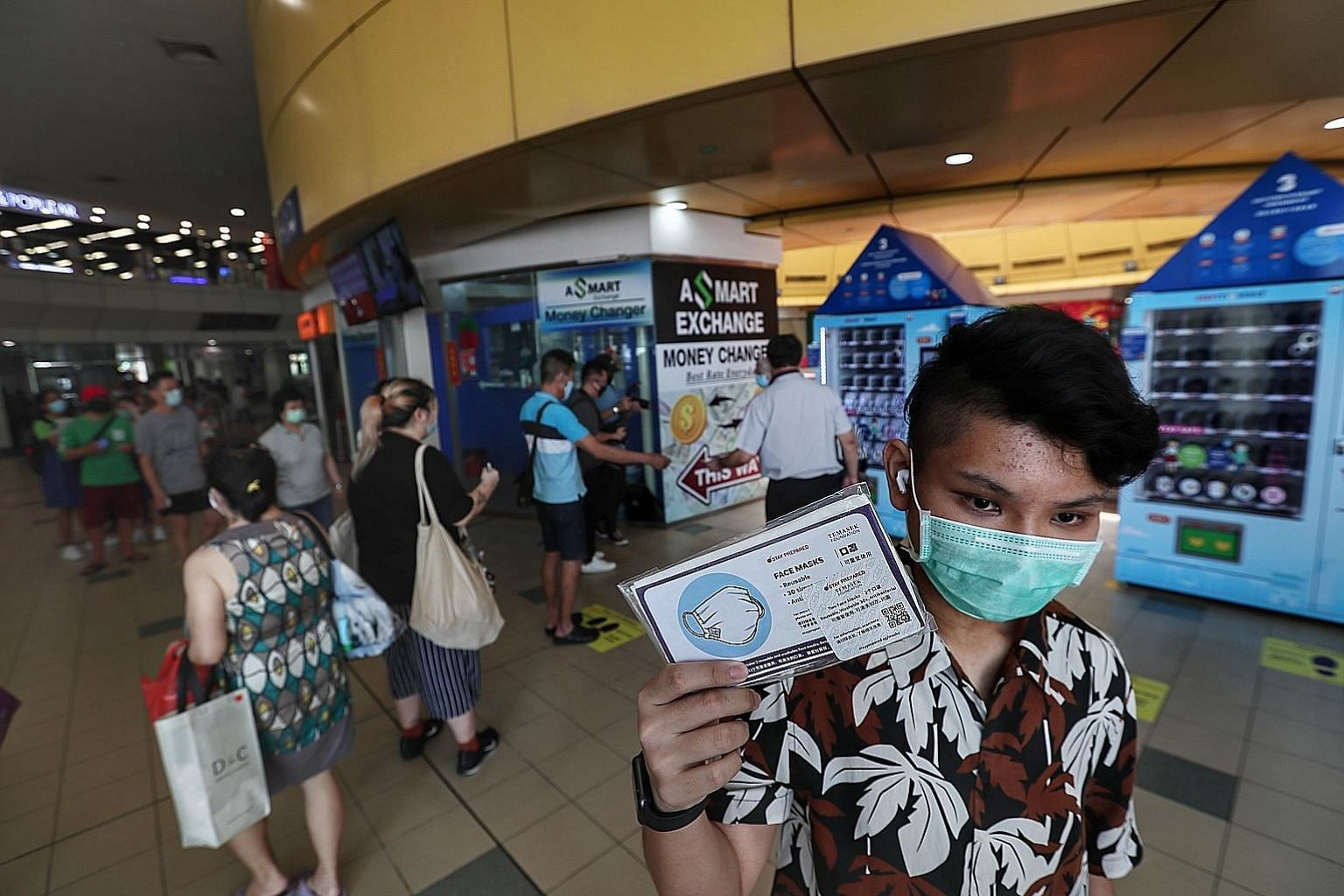 Thai national Pirapat, 17, a student in Singapore, with a free reusable mask from Temasek Foundation collected from a vending machine at the Toa Payoh bus interchange in June. A total of 11 million masks were given out to residents here. ST PHOTO: KE