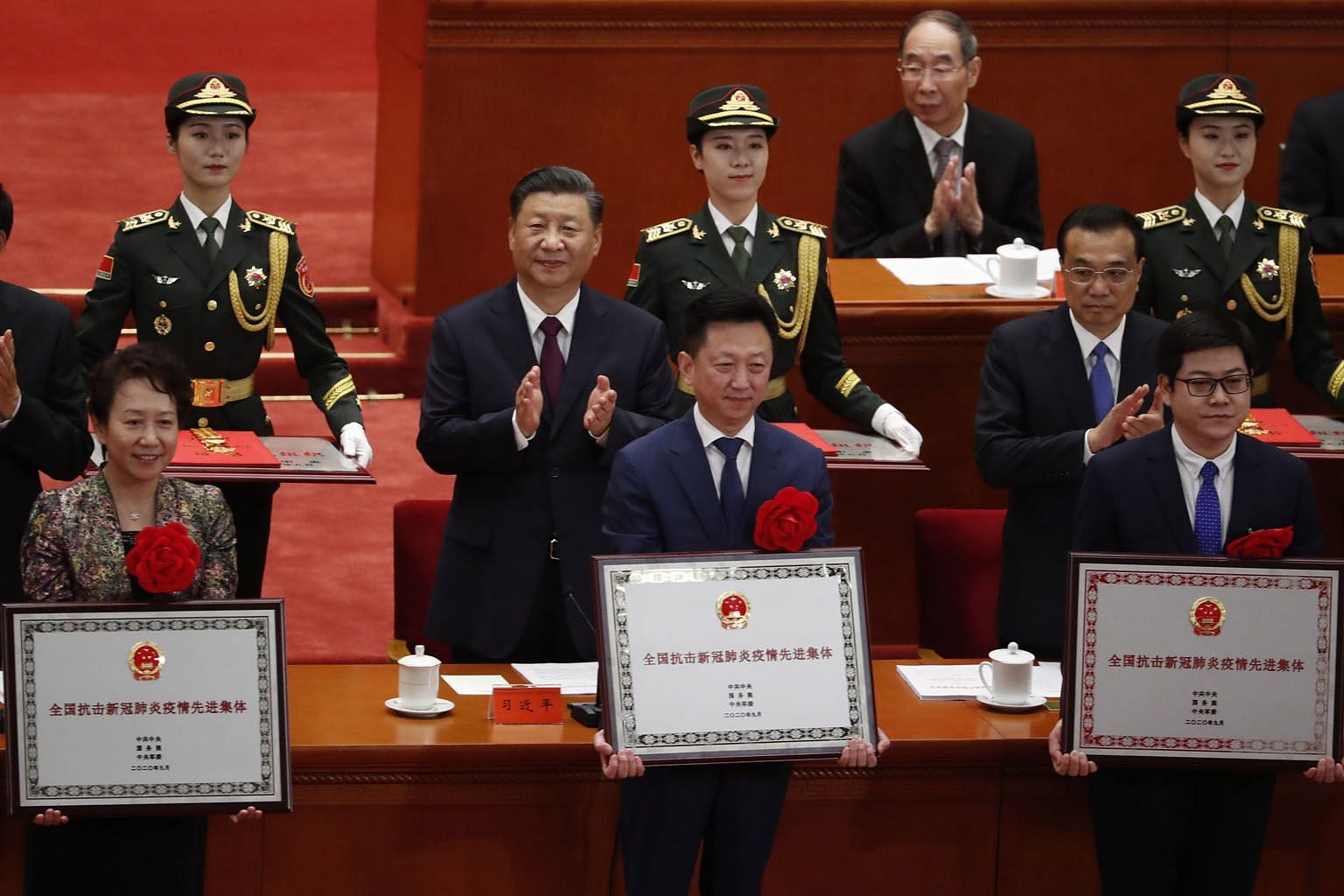 Chinese President Xi Jinping and Premier Li Keqiang (both middle row) clapping as the country bestowed honours on the people who contributed to the fight against the coronavirus. More than 2,000 people were given awards at a ceremony held at the Grea